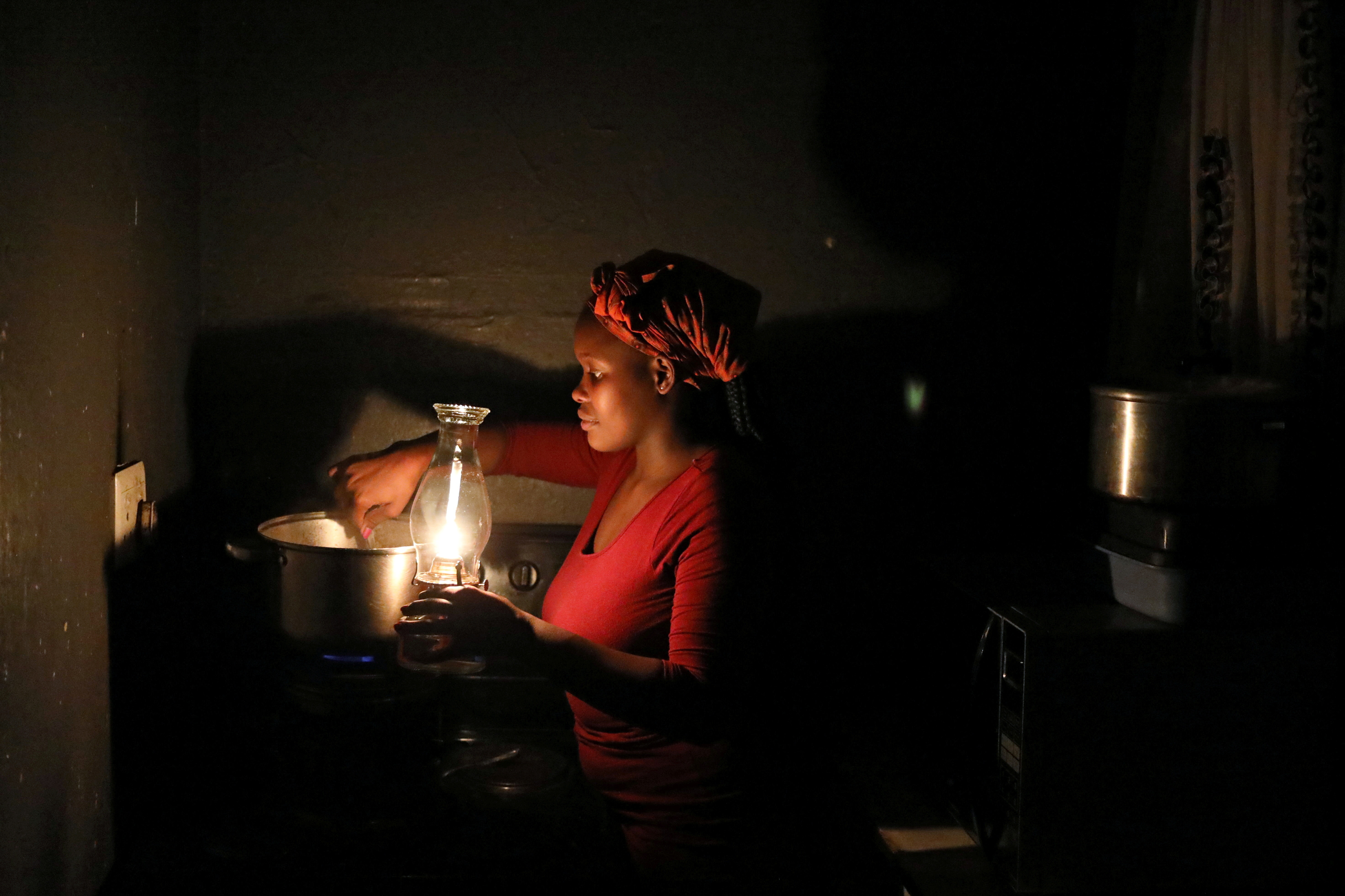 Luyanda Makhathini uses a parafin light while cooking during an electricity load-shedding blackout at her home in Soweto, South Africa, March 18, 2021. REUTERS/Siphiwe Sibeko