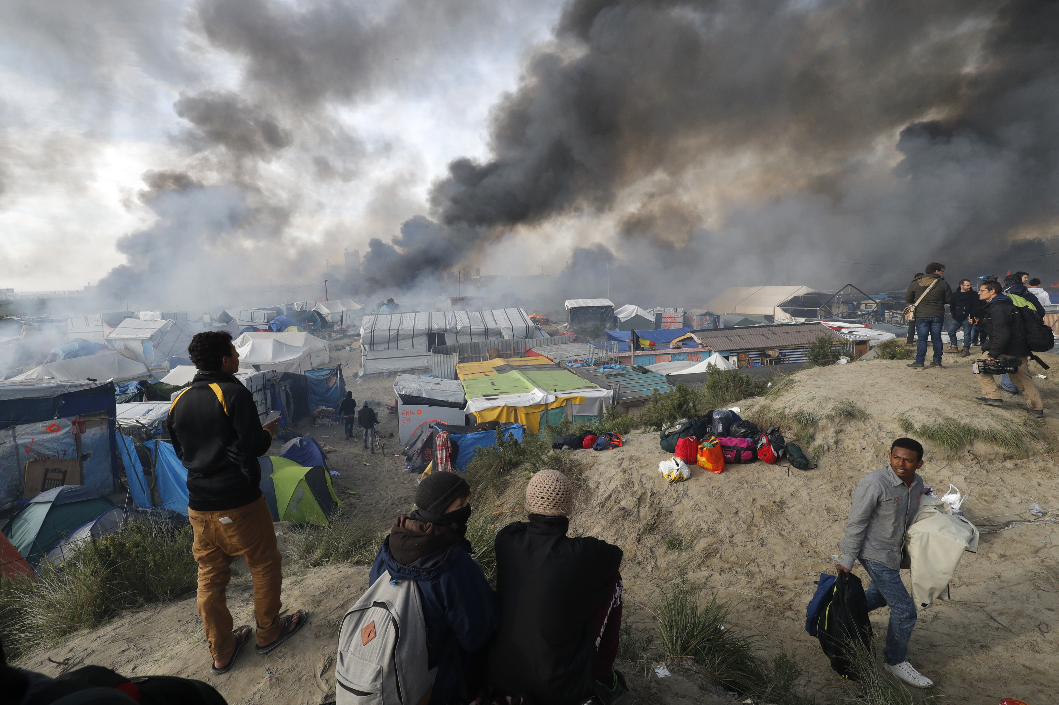 "Smoke rises the sky as migrants and journalists look at burning makeshift shelters and tents in the ""Jungle"" on the third day of their evacuation and transfer to reception centers in France, as part of the dismantlement of the camp in Calais, France, October 26, 2016.          REUTERS/Philippe Wojazer TPX IMAGES OF THE DAY - LR1ECAQ0UA87V"