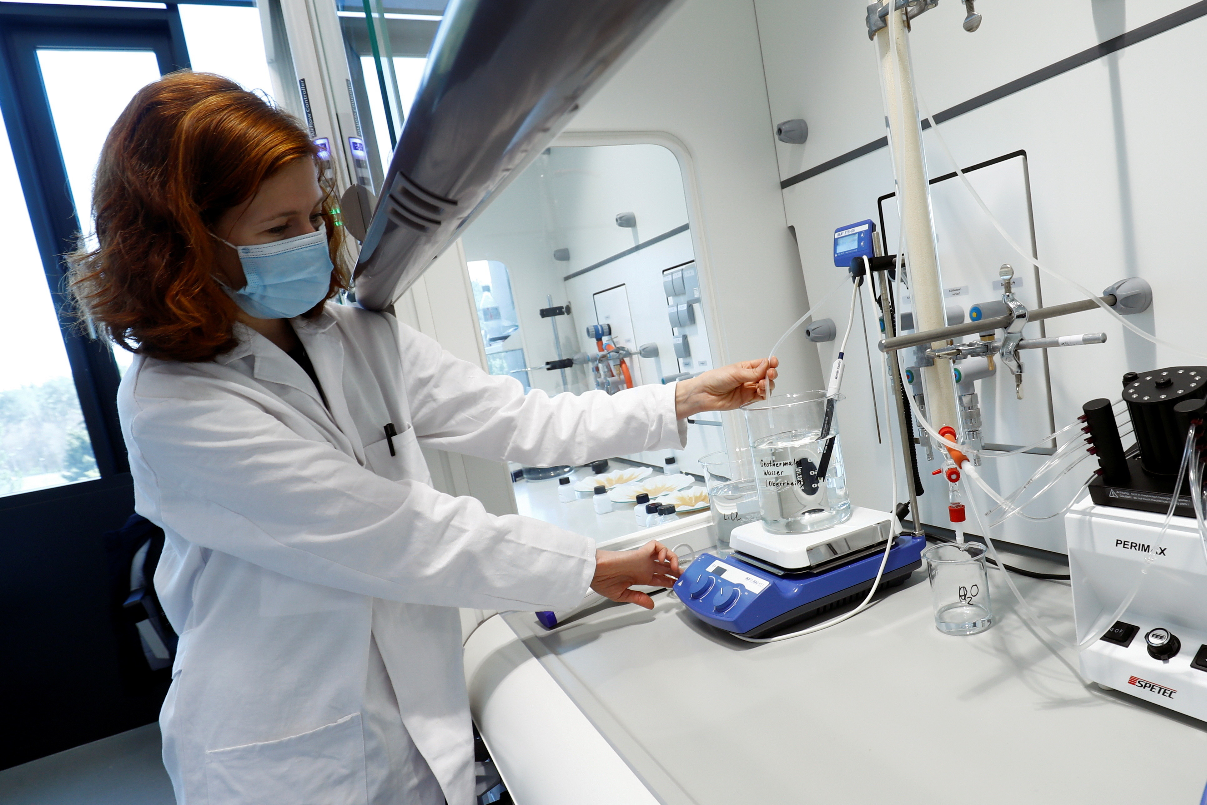 A woman dressed in a lab coat tends to a scientific experiment.