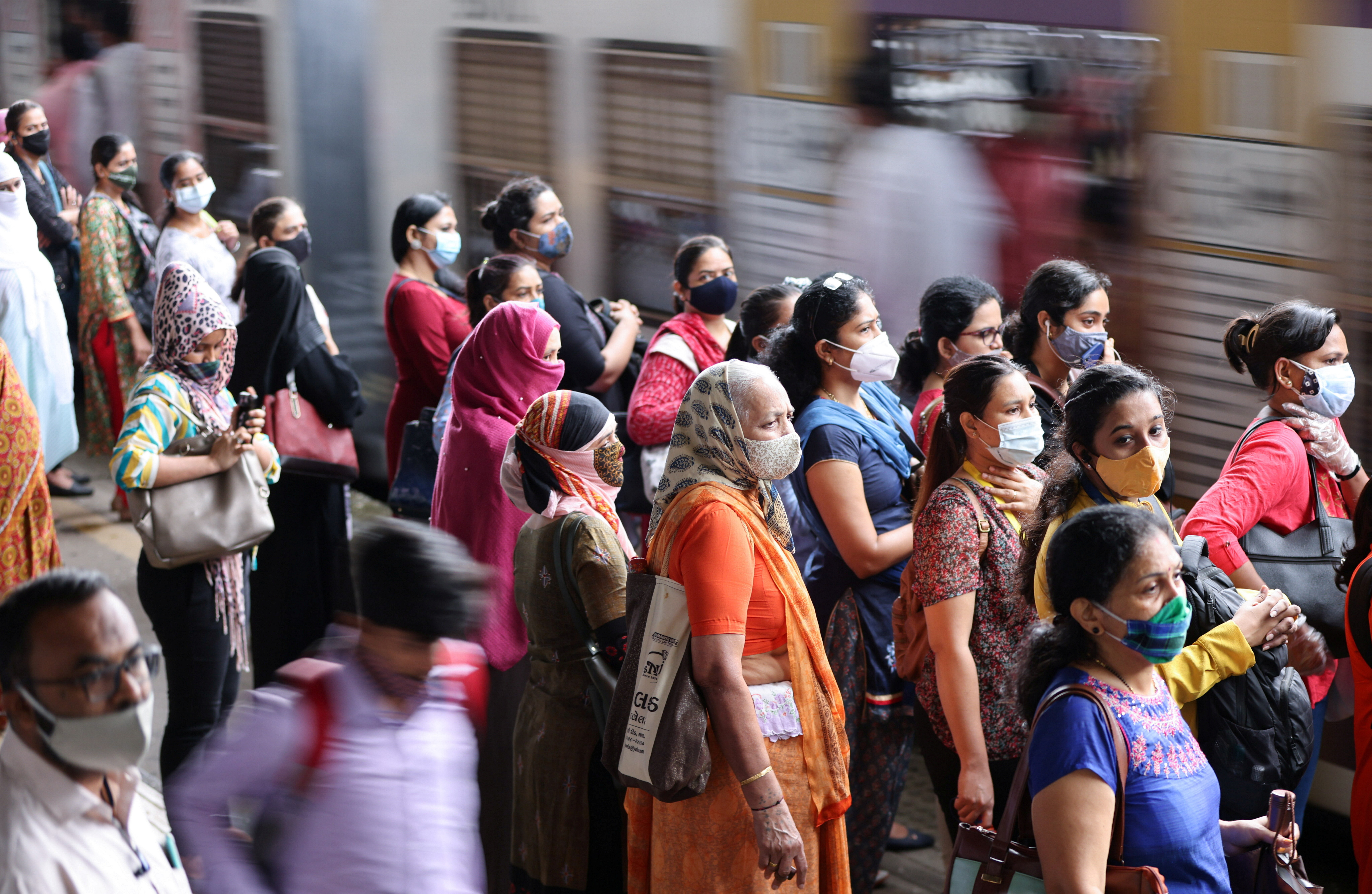 Commuters wearing protective face masks wait to board a suburban train after authorities resumed train services for vaccinated passengers amid the coronavirus disease (COVID-19) pandemic, in Mumbai, India, August 17, 2021. REUTERS/Francis Mascarenhas - RC2R6P9CHMC0