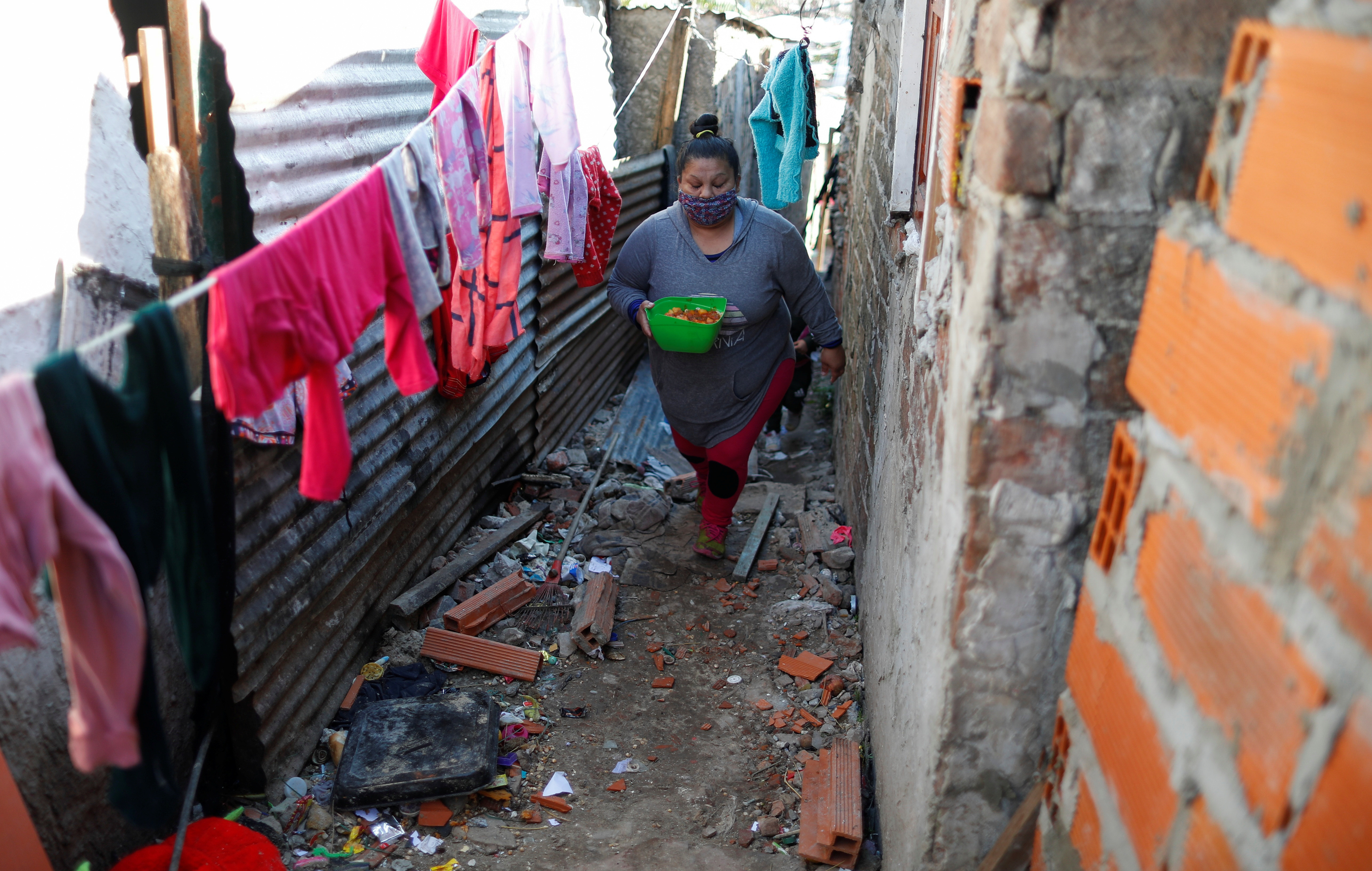 Silvia Puntano walks to her home after receiving a ration of stew in a plastic container at a soup kitchen, during the coronavirus disease (COVID-19) outbreak, in Villa Azul, on the outskirts of Buenos Aires, Argentina July 29, 2020. Picture taken July 29, 2020. REUTERS/Agustin Marcarian - RC2N7I9PV7QI