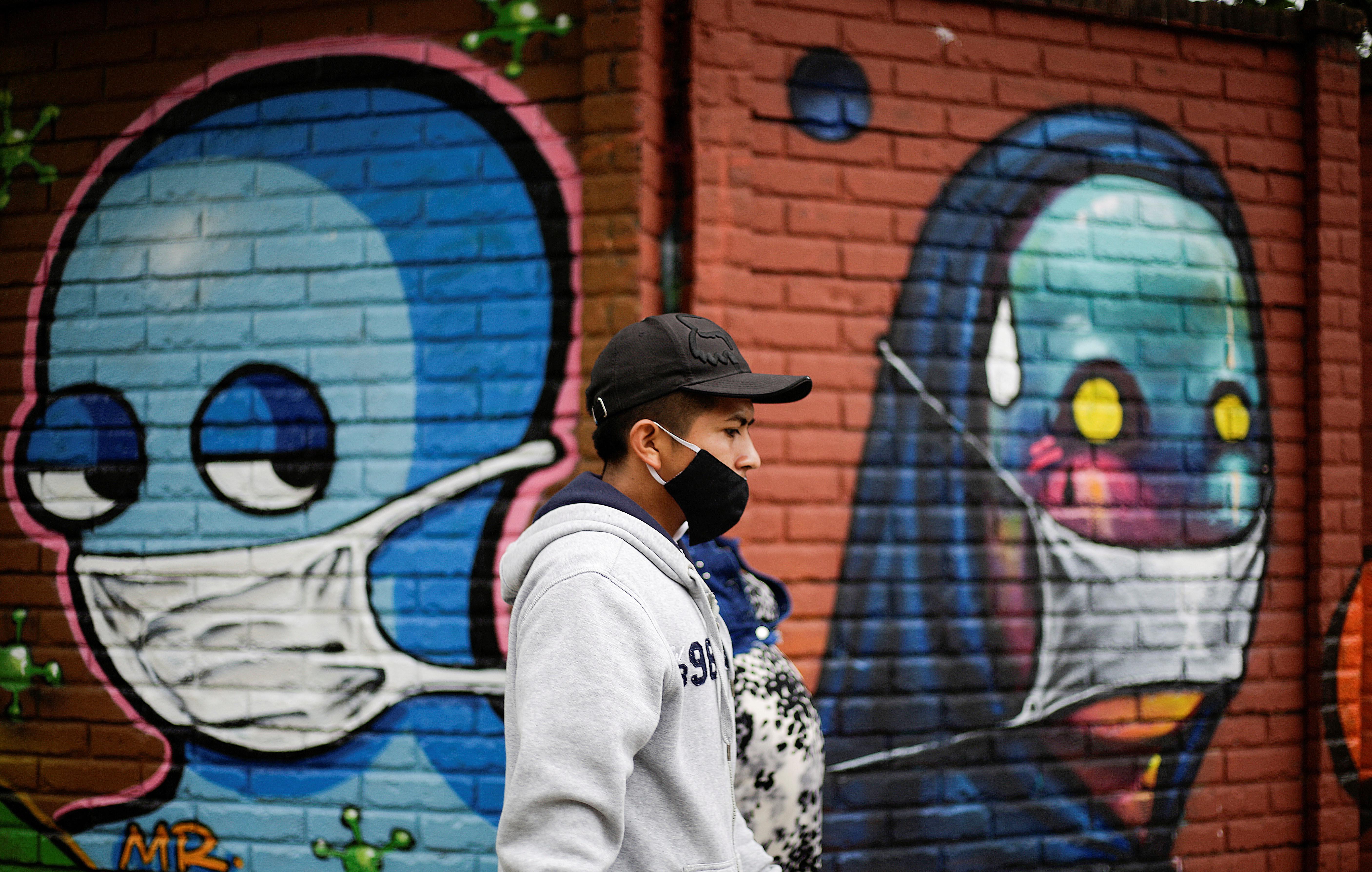 Un hombre con una mascarilla facial camina junto a una pared con graffitis después de que las autoridades sanitarias revocan las medidas de reapertura tras el aumento de los casos de la enfermedad coronavirus (COVID-19) en San José (Costa Rica) el 13 de julio de 2020.