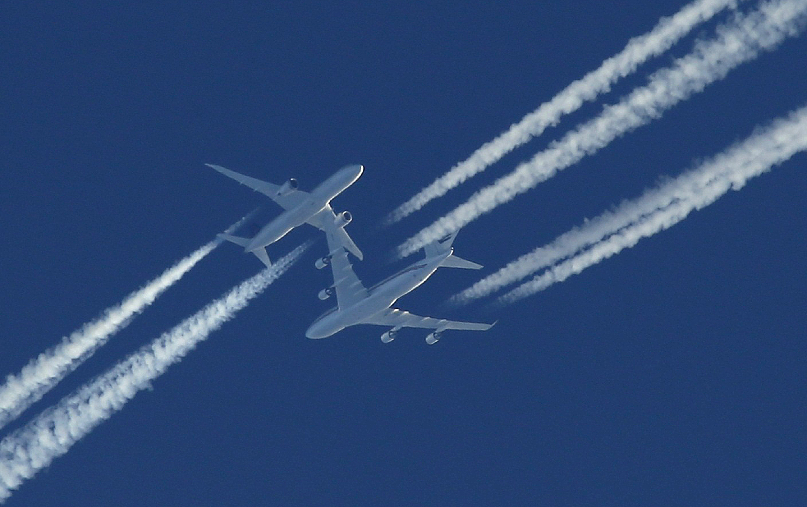Two airline planes pass each  other in the sky going opposite directions