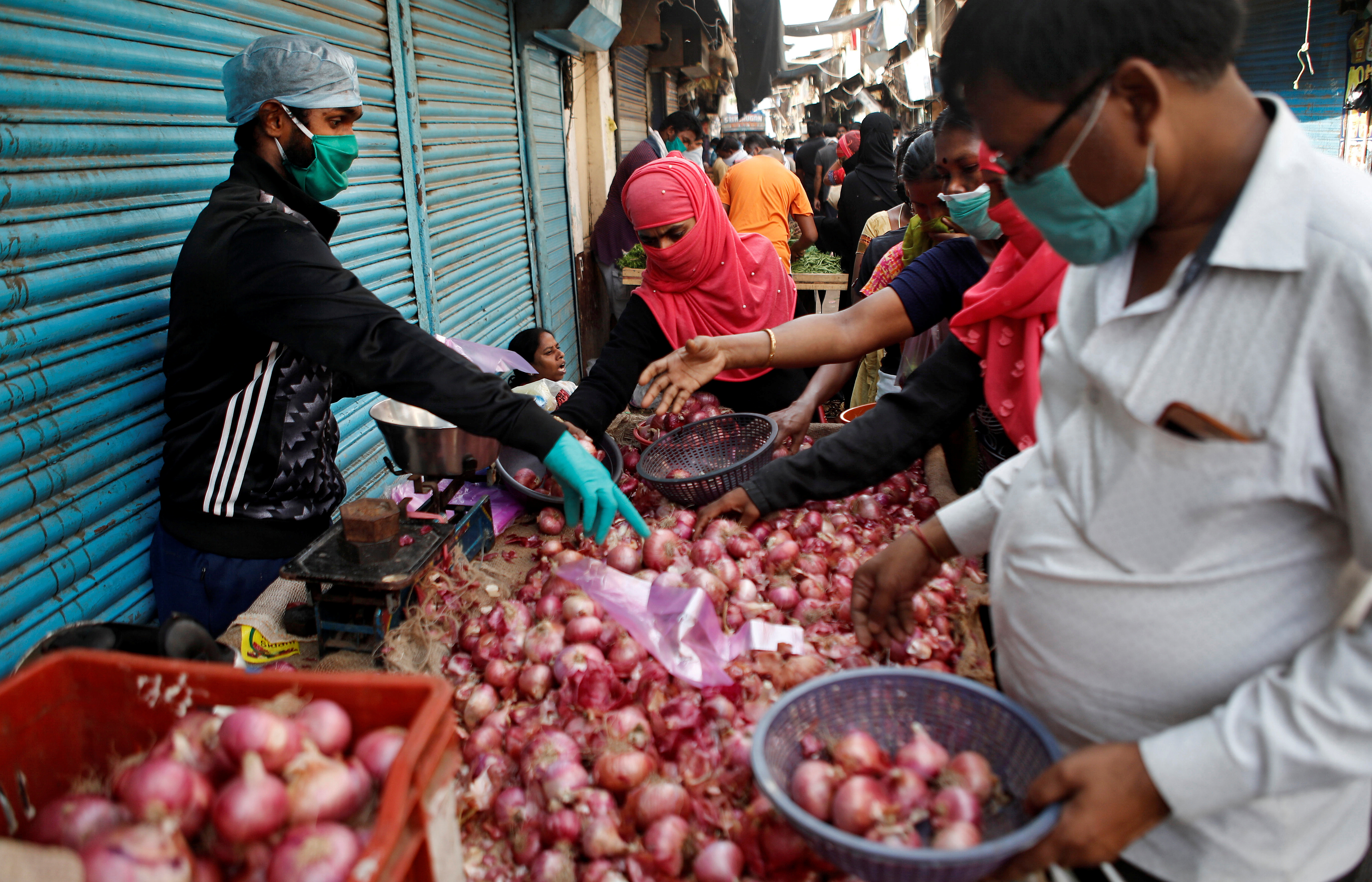 People buy onions at a market in the slum of Dharavi, Mumbai.