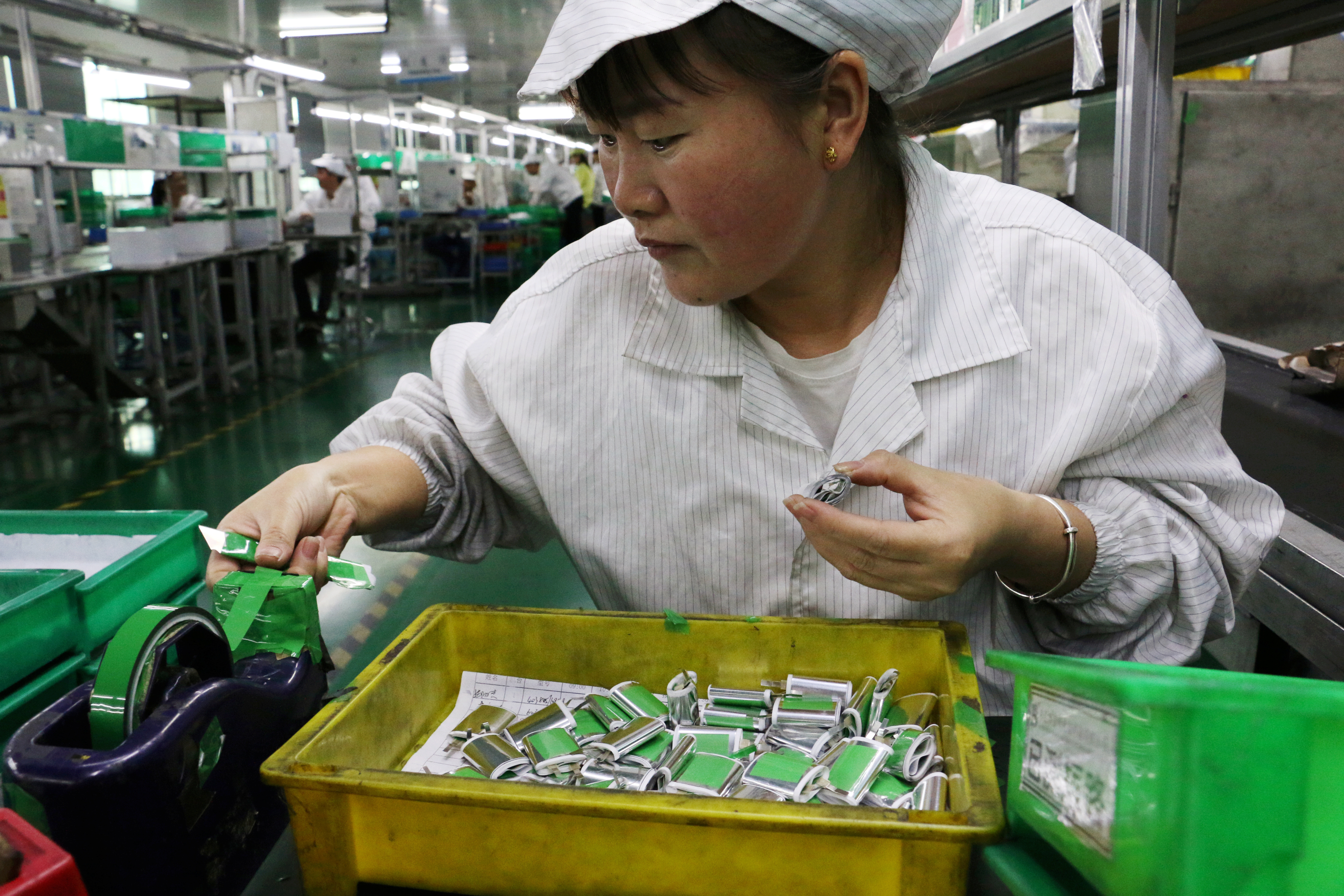 image of an employee working at a production line of lithium ion batteries inside a factory in Dongguan, Guangdong province, China