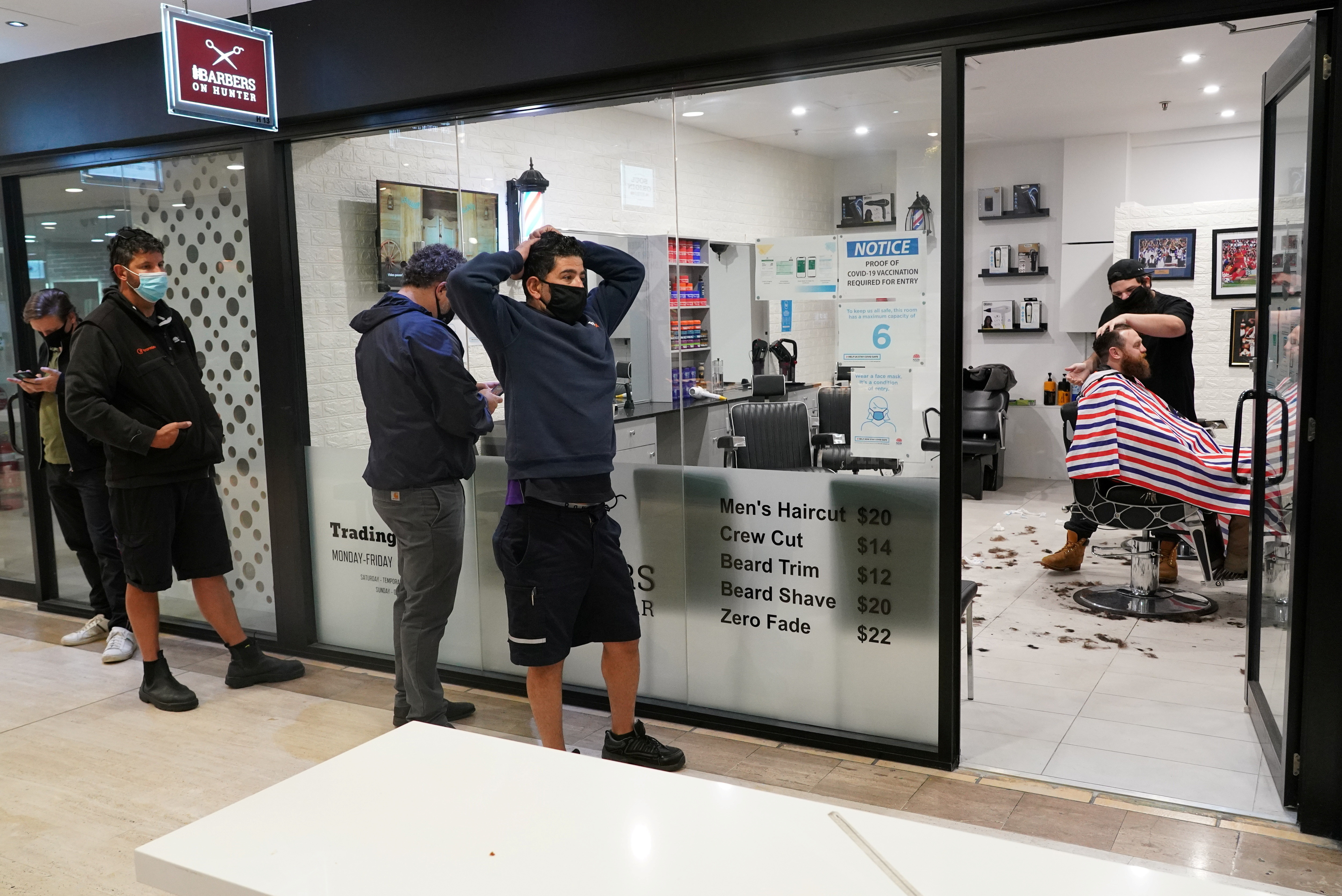 Customers wait in line at a city centre barber shop on the first day of many such businesses re-opening to vaccinated patrons, following months of lockdown orders that closed businesses to curb an outbreak of the coronavirus disease (COVID-19), in Sydney, Australia, October 11, 2021.  REUTERS/Loren Elliott - RC2C7Q9PQEAP
