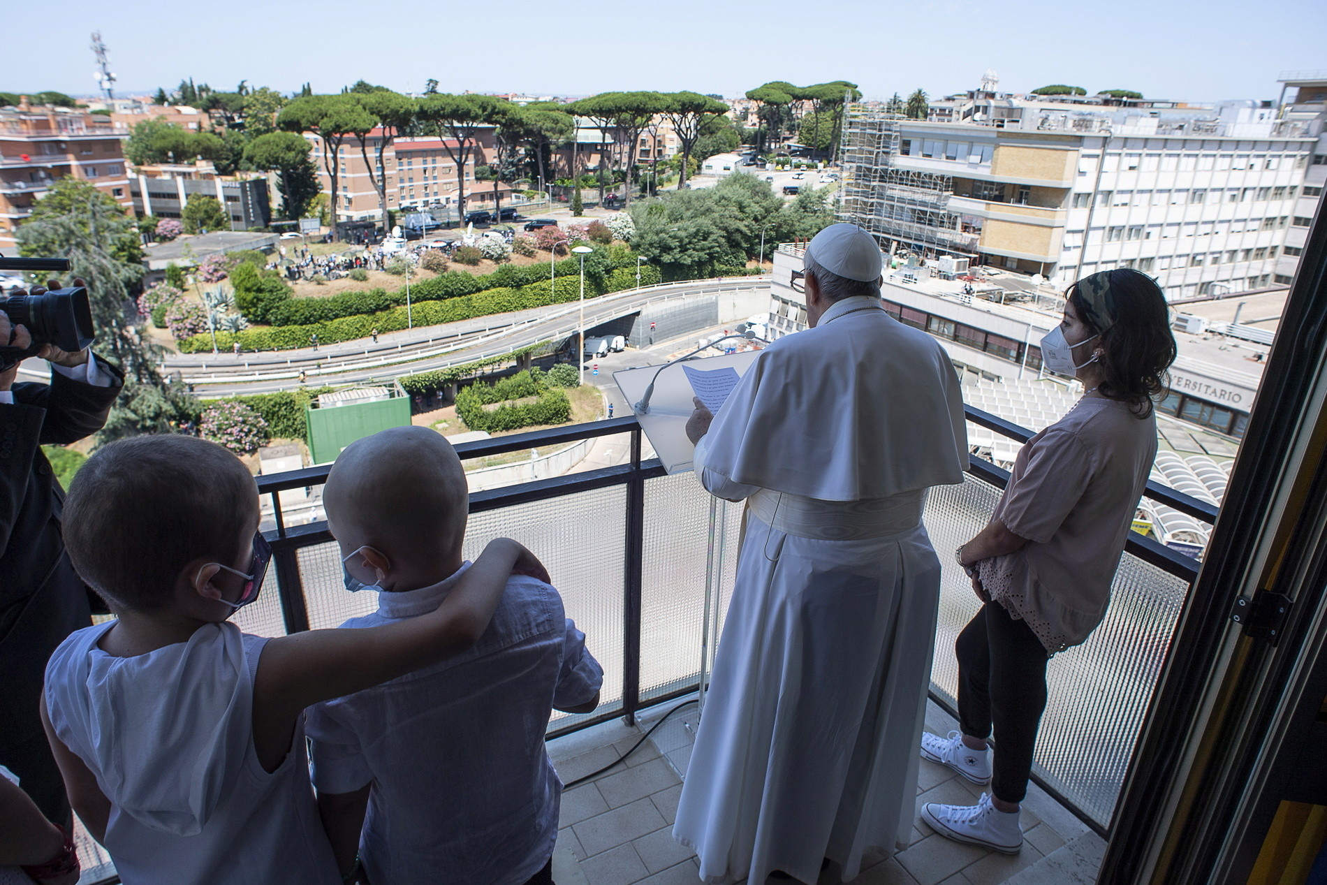 Children accompany Pope Francis as he leads the Angelus prayer from a balcony of the Gemelli hospital, as he recovers following scheduled surgery on his colon, in Rome, Italy