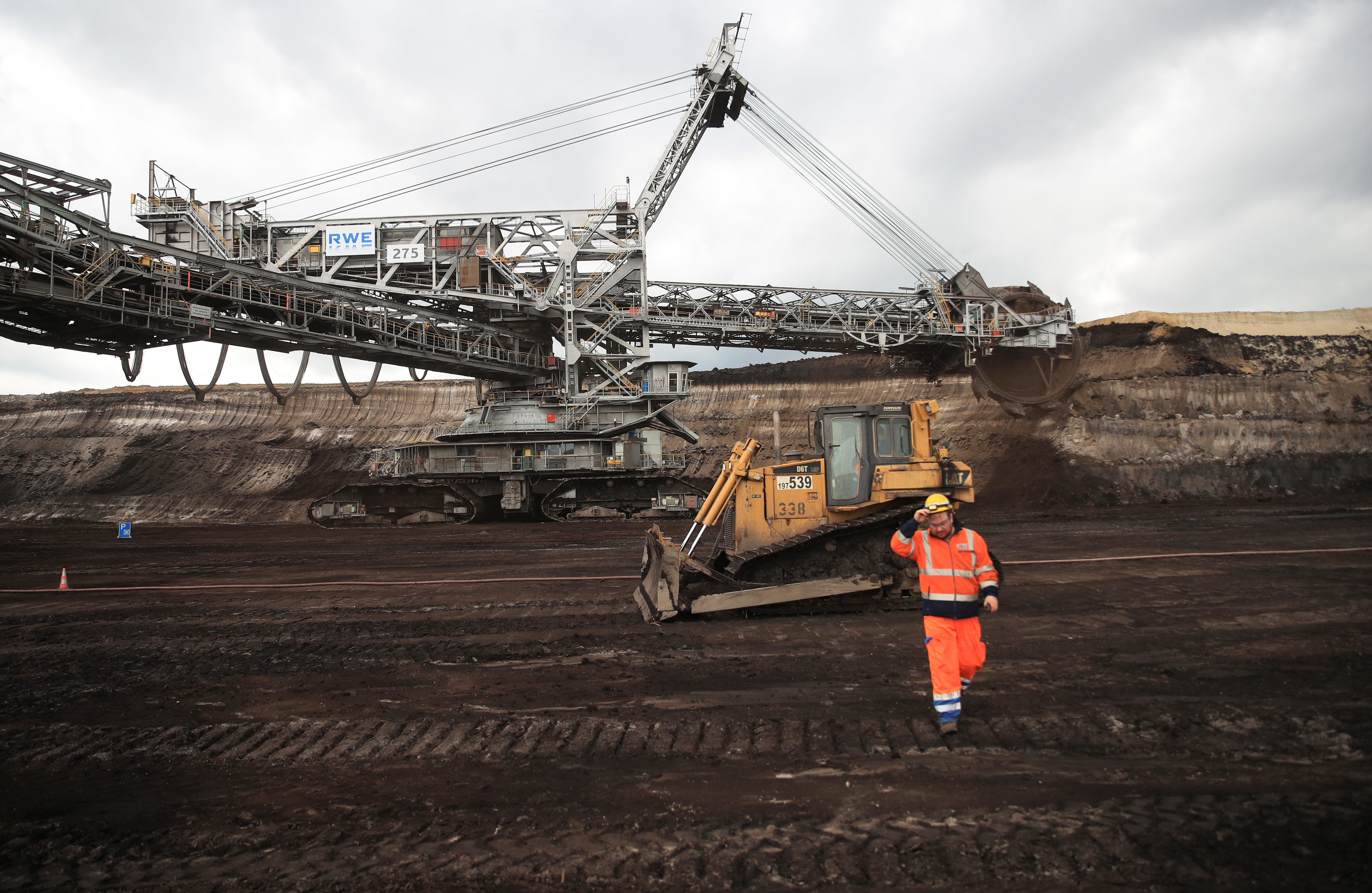 An operator of RWE's huge bucket wheel excavator lifts his helmet while the paddle-wheel digs for lignite in the open-cast brown coal mine of Inden near Weisweiler after an Internet auction ended to sell the 3,500 tons heavy excavator in Inden, Germany September 30, 2020
