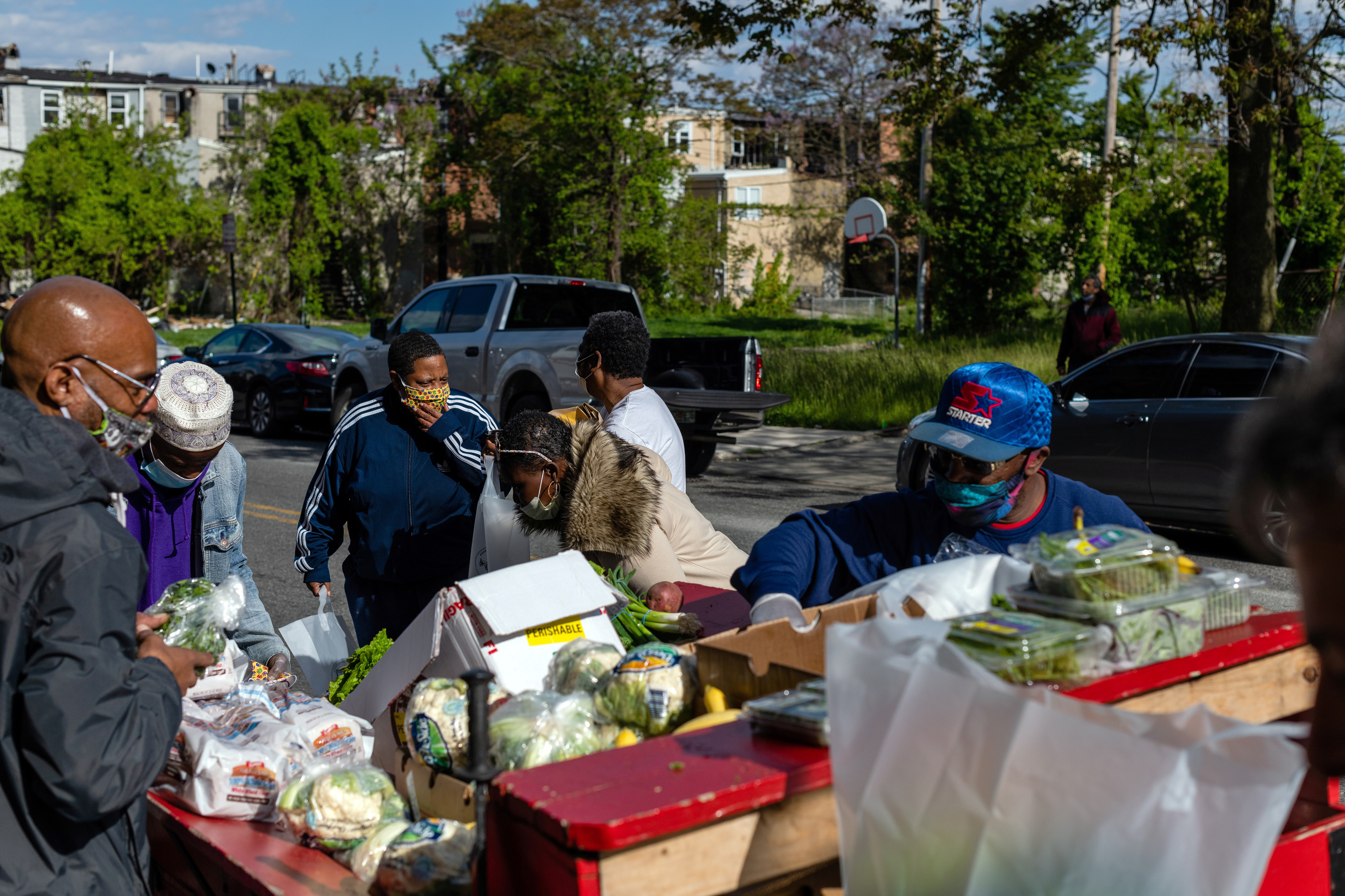 Residents pick out supplies at a food giveaway in West Baltimore amid the coronavirus outbreak.