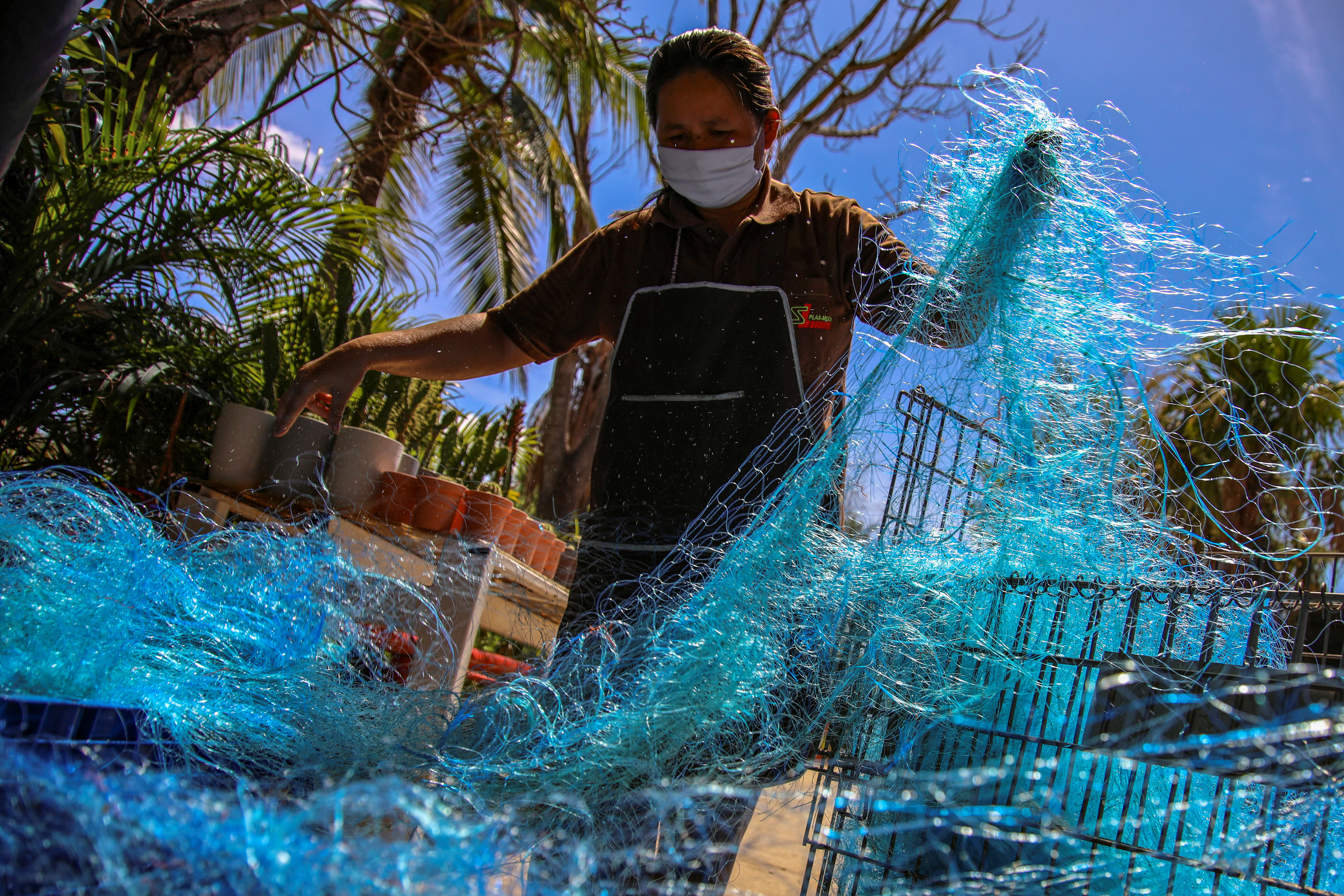 A worker prepares old fishing nets before a recycling process to create, among new products, protective gear against the coronavirus disease (COVID-19) at the Saint Louis Plas Mold factory amid the COVID-19 outbreak in Ayutthaya province, Thailand, June 30, 2020. Picture taken June 30, 2020. REUTERS/Juarawee Kittisilpa - RC2YKH98ALLO