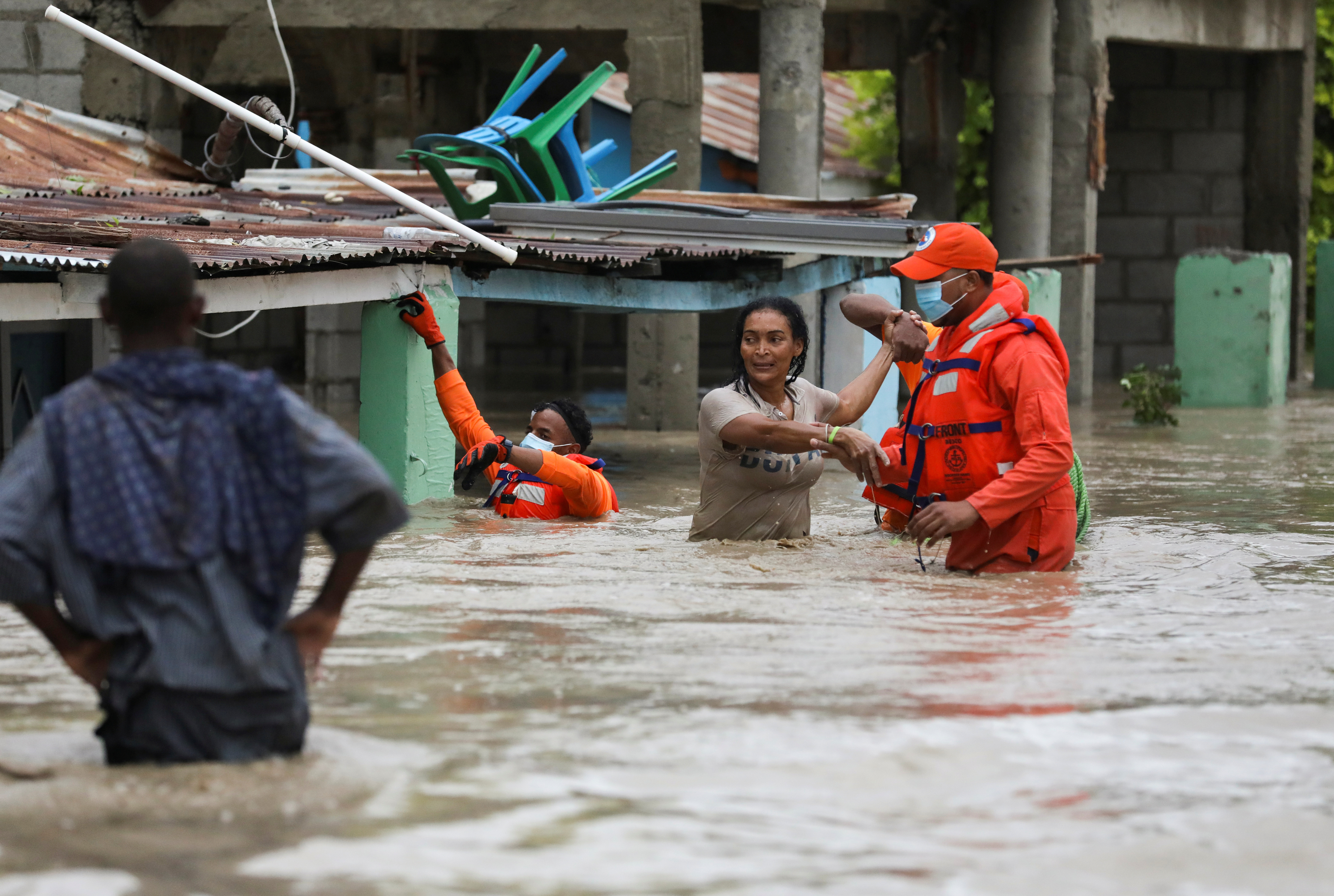 Members of the Civil Defence help a woman in a flooded street after the passage of Storm Laura, in Azua, Dominican Republic August 23, 2020. REUTERS/Ricardo Rojas - RC21KI9M1R9X