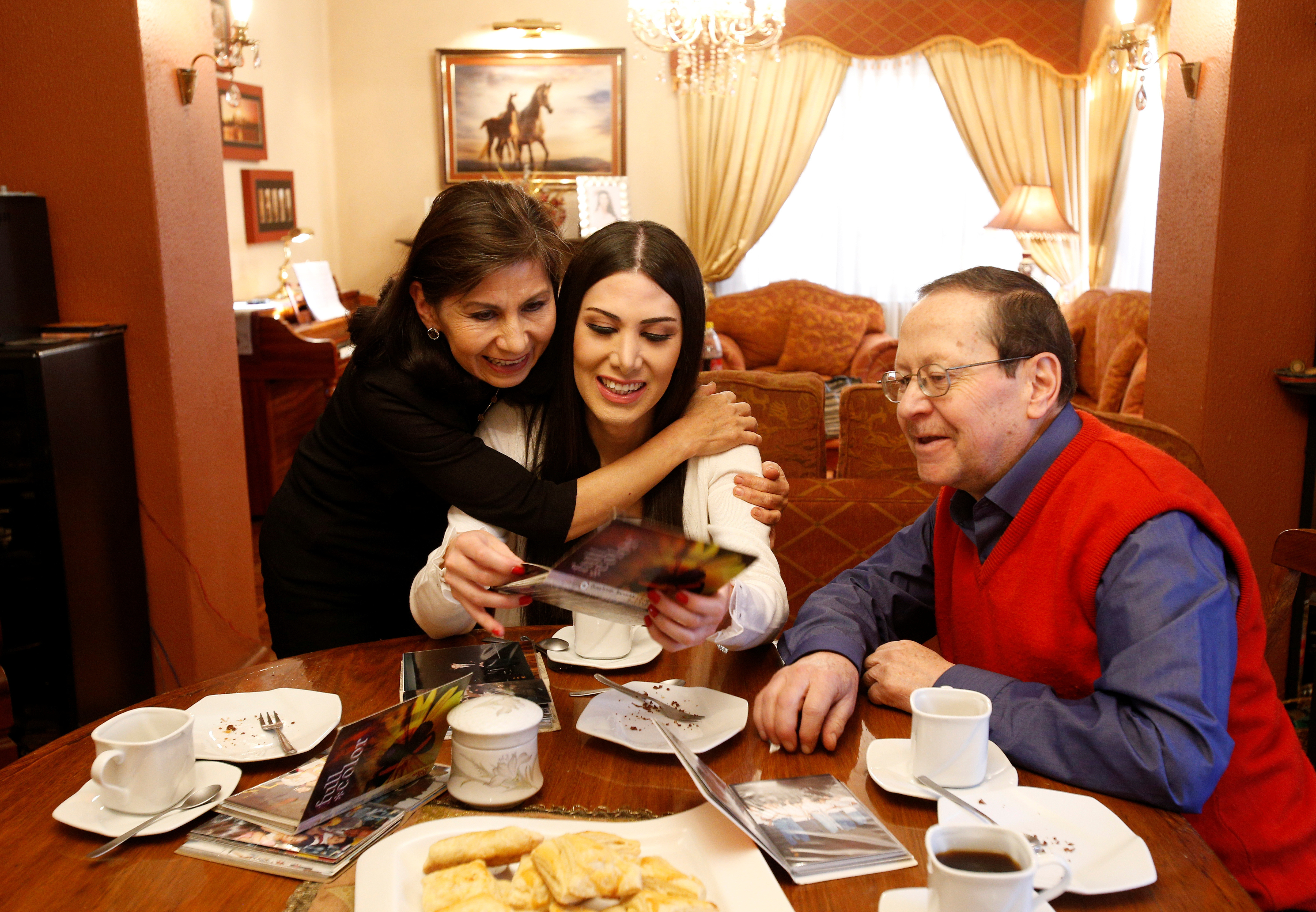 Leonie Dorado, a transgender news anchor, looks at family photos with her parents Carol Arce and Hugo Dorado at her home, amid the outbreak of coronavirus disease (COVID-19), in La Paz, Bolivia, July 1, 2020. Picture taken July 1, 2020. REUTERS/David Mercado - RC2DOH91DSBG