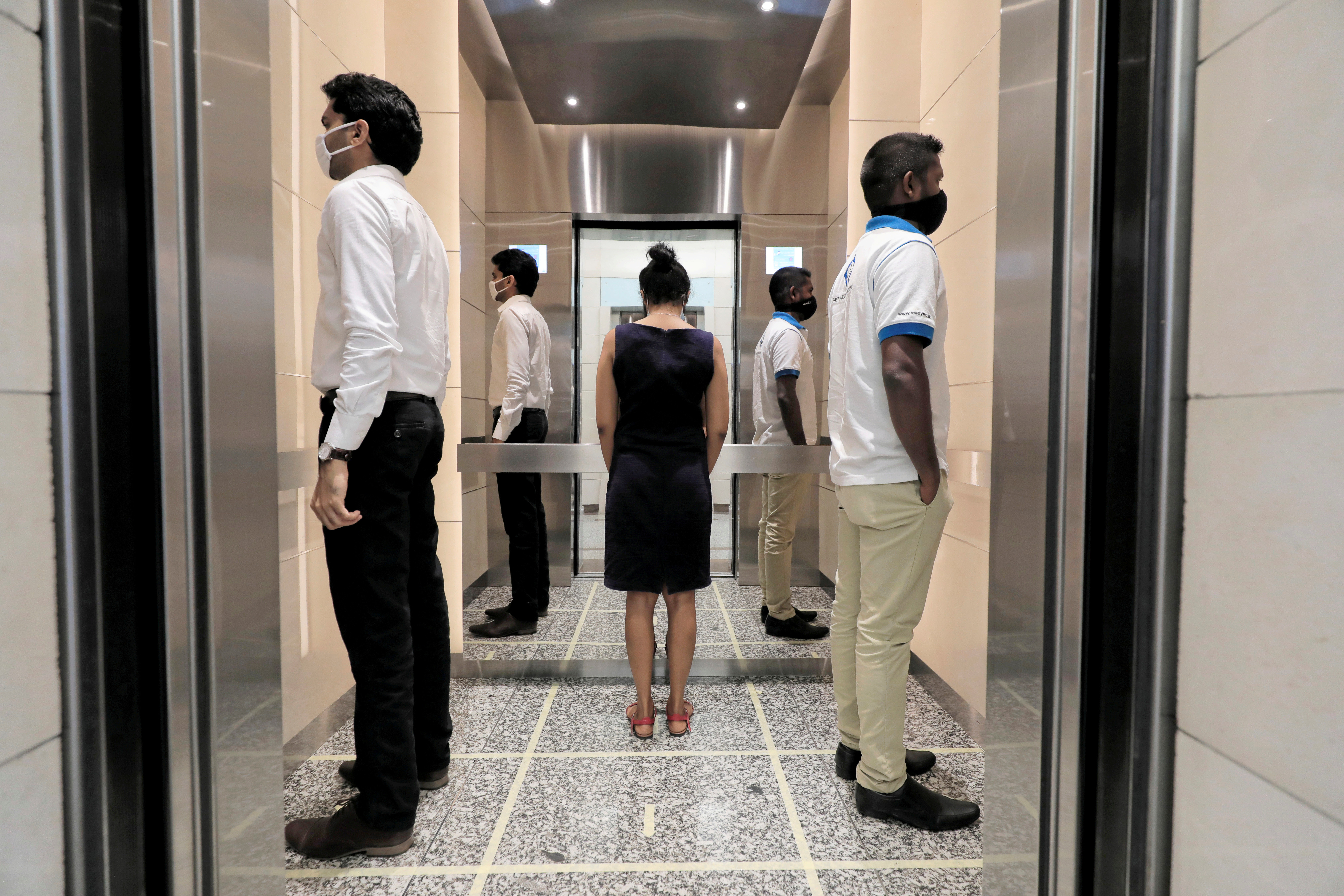 People practice social distancing inside an elevator prior to arriving to their work places at World Trade Center, after the government announced that private and state companies will reopen their offices after almost two months of lockdown amidst concerns about the spread of coronavirus disease (COVID-19) in Colombo, Sri Lanka May 11, 2020. REUTERS/Dinuka Liyanawatte     TPX IMAGES OF THE DAY - RC29MG9B5S3U