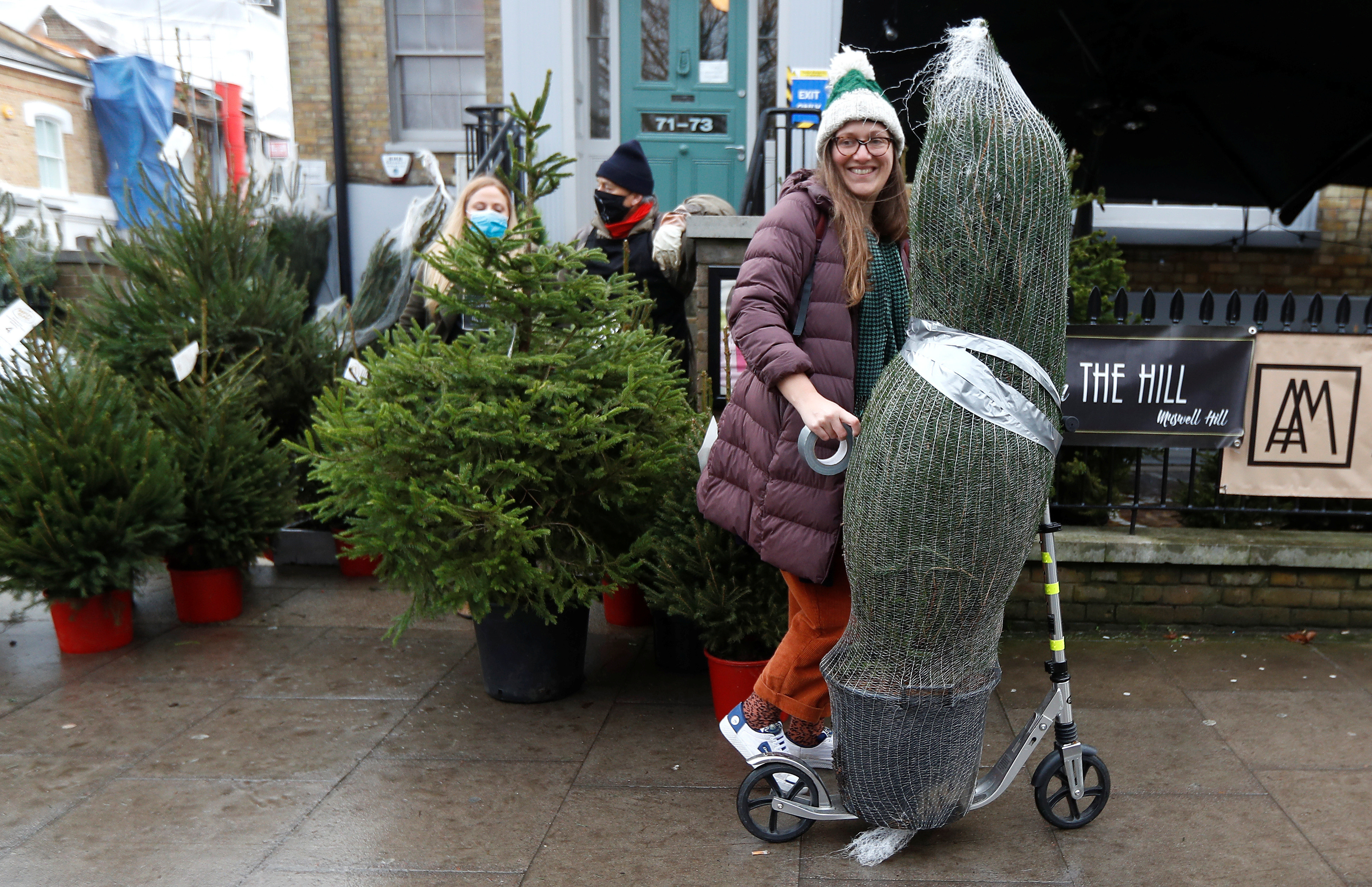 A woman who rented a Christmas tree from Christmas on The Hill carries her tree away on a scooter, in London, Britain, December 12, 2020. Picture taken December 12, 2020.