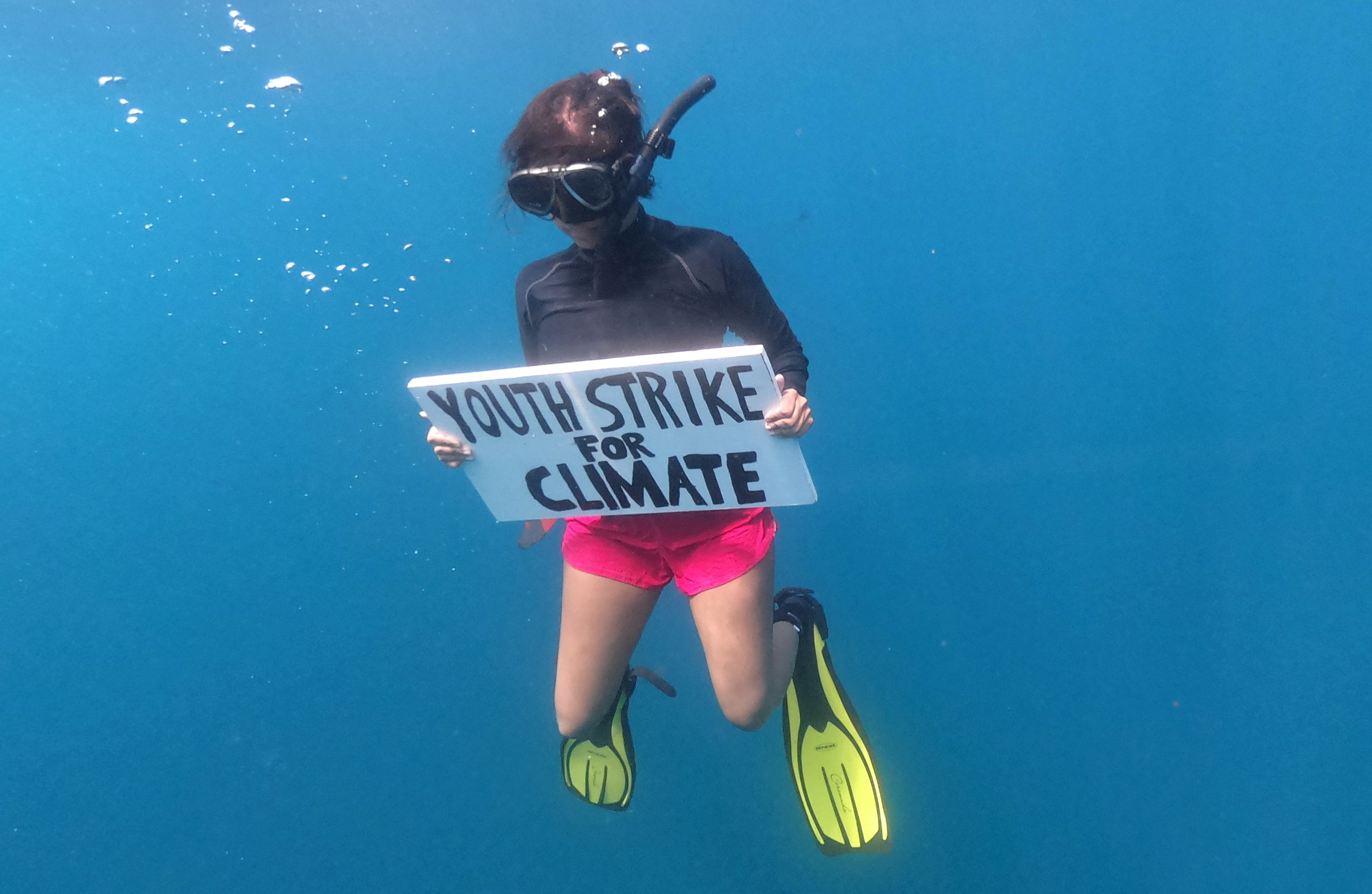 Mauritian scientist and climate change activist Shaama Sandooyea 24, holds a placard reading Youth Strike For Climate, during an underwater protest at the Saya de Malha Bank to highlight the need to protect the world's largest seagrass meadow within the Mascarene plateau, Mauritius March 6, 2021. Picture taken March 6, 2021.