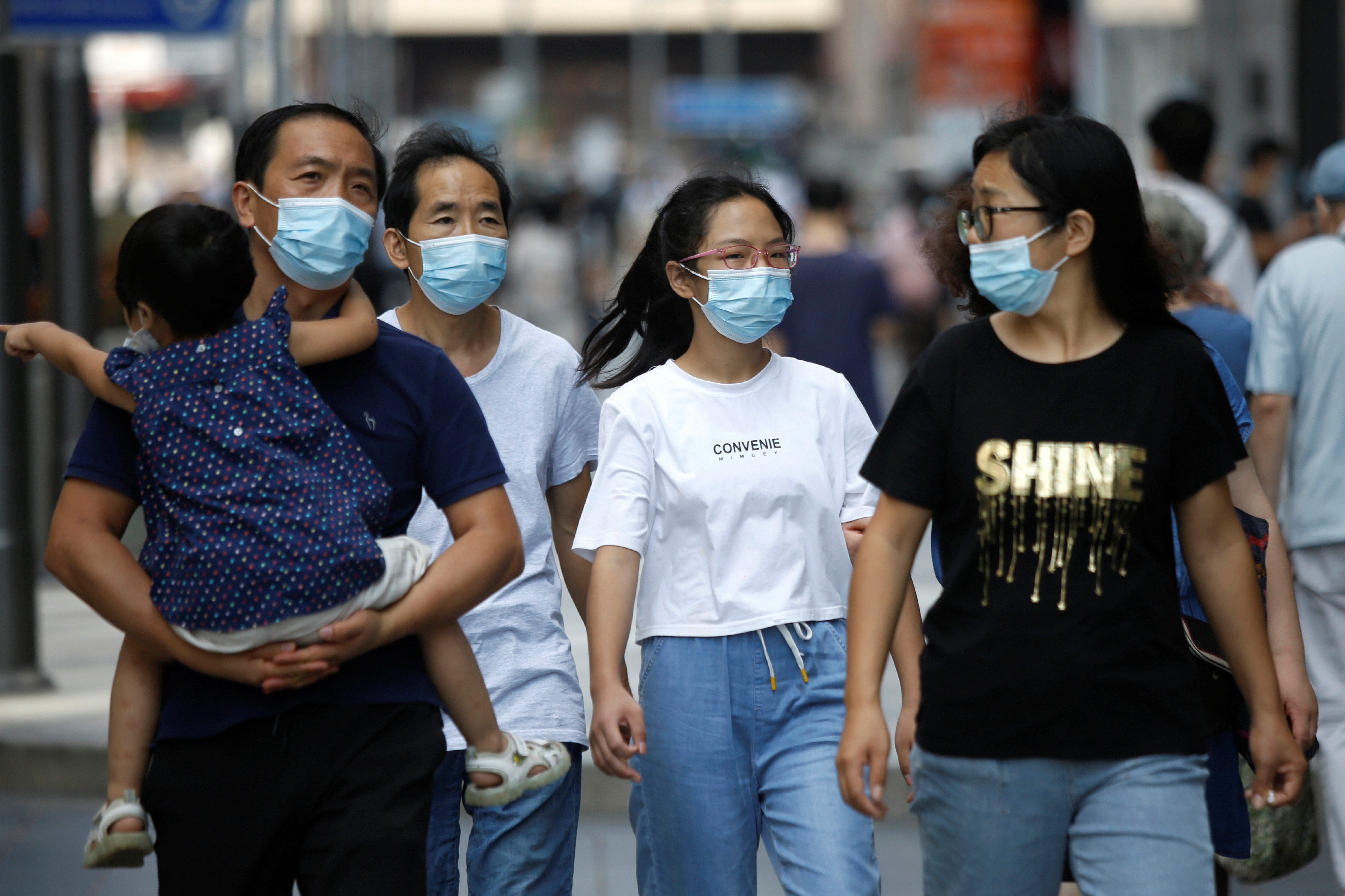 People wearing face masks walk at a shopping area, after Beijing Centre for Disease Prevention and Control announced that wearing face masks are no longer mandatory outdoor in Beijing, following the coronavirus disease (COVID-19) outbreak, China August 21, 2020. REUTERS/Tingshu Wang - RC25II9FQLSJ