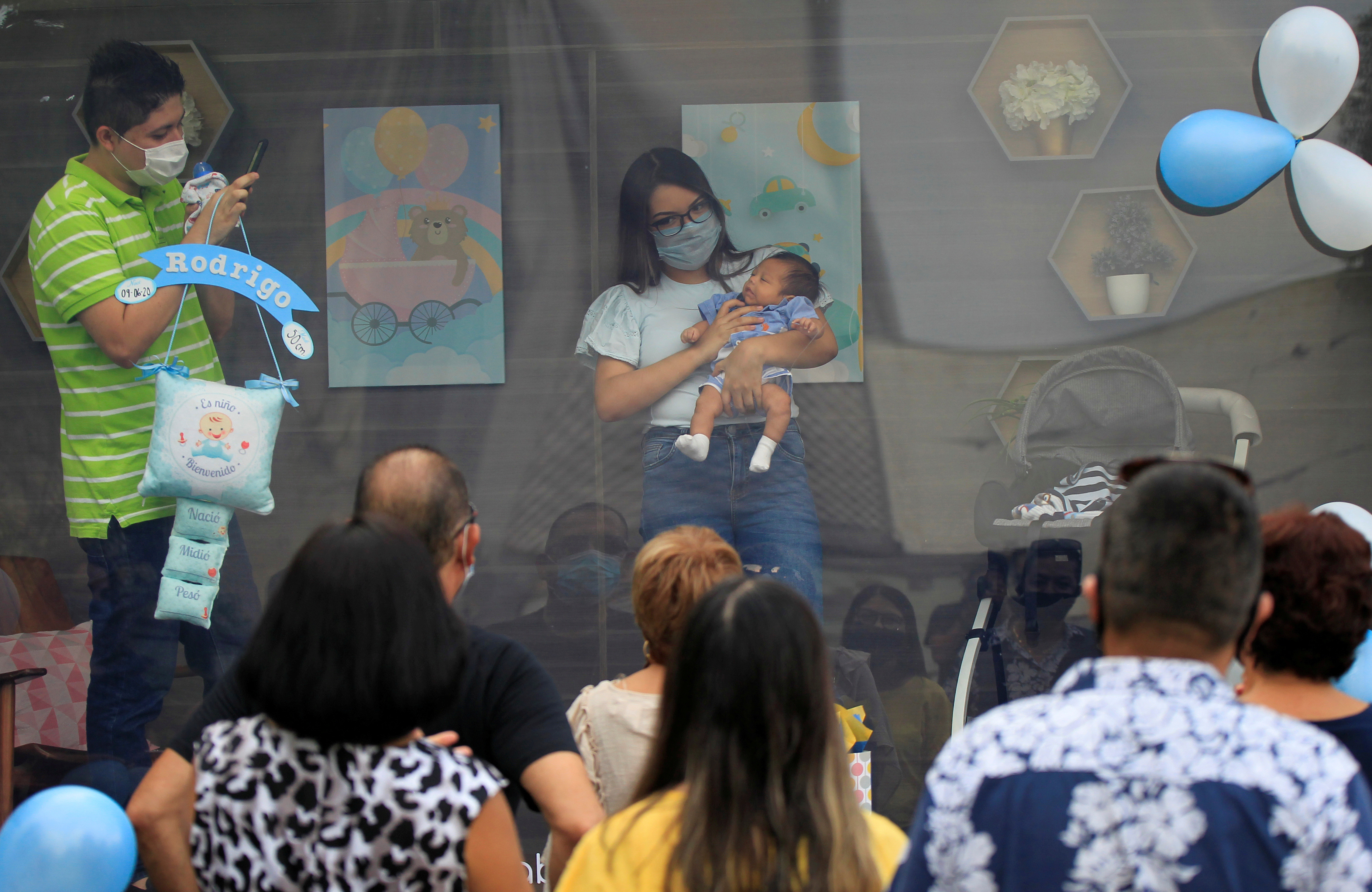 """A couple is seen with their newborn baby inside a sanitized cabin called """"Baby Cabin Parade"""" to show the newborn to relatives as a social distancing solution during the coronavirus disease (COVID-19) outbreak in Monterrey, Mexico July 31, 2020. Picture taken July 31, 2020. REUTERS/Daniel Becerril     TPX IMAGES OF THE DAY - RC2B5I9WR6QO"""