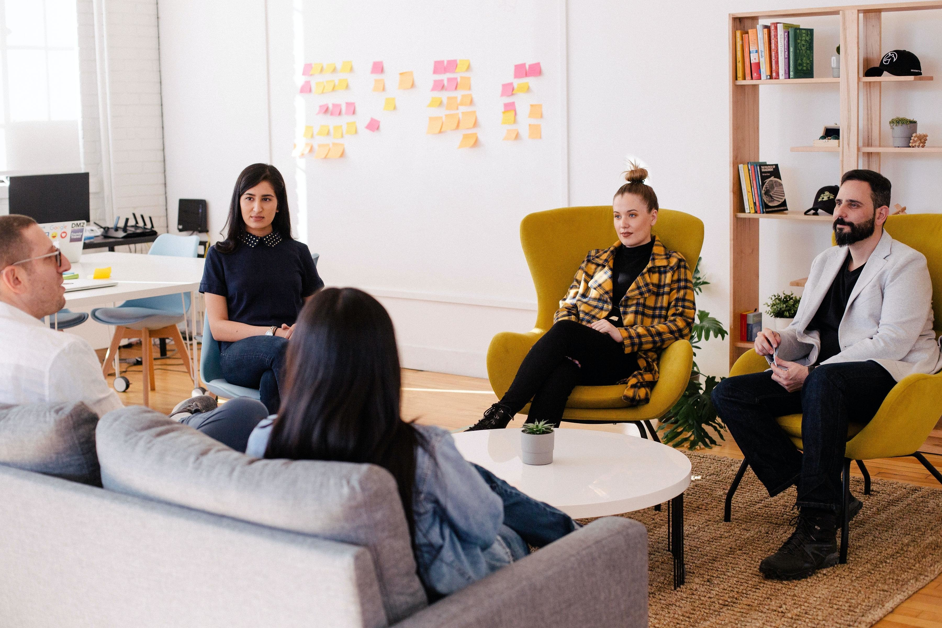 a group of young professionals sit around in an office environment