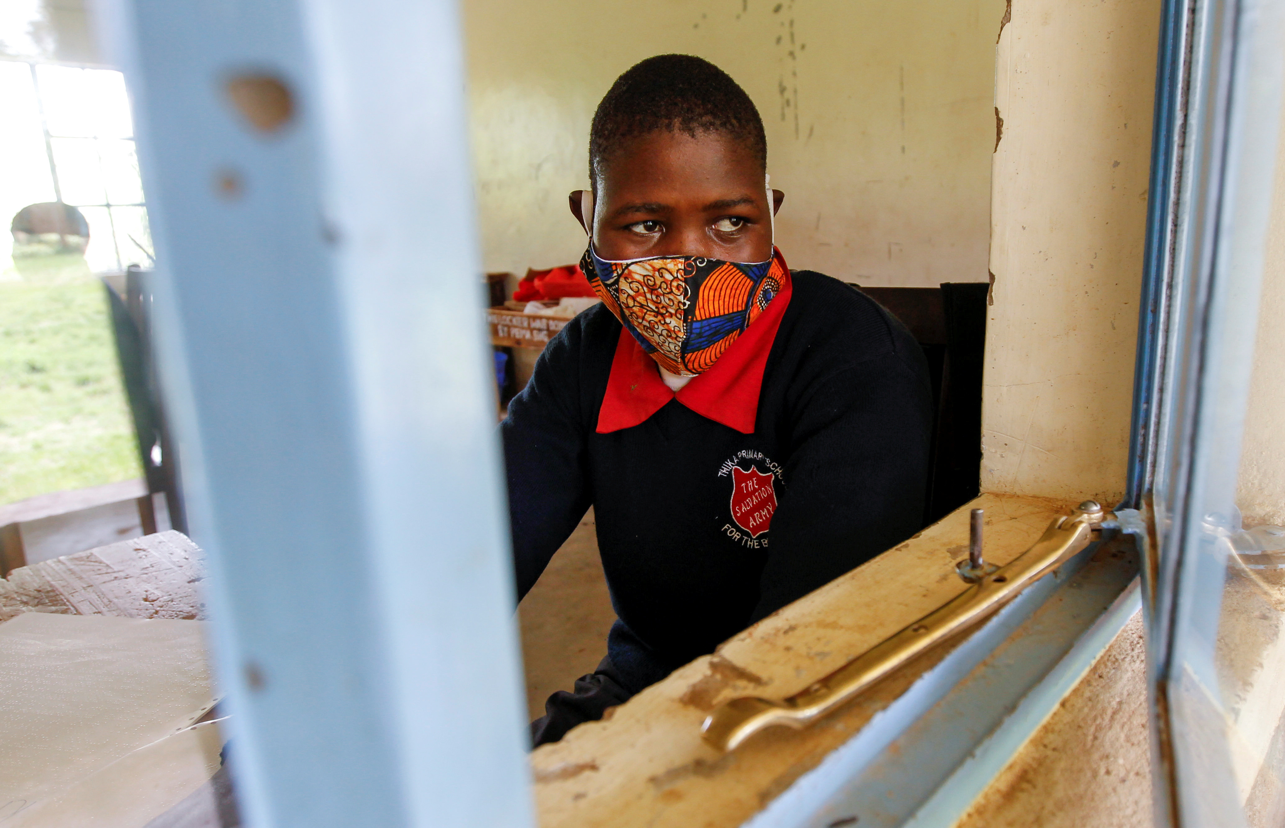A Kenyan pupil attends a lesson, wearing a protective mask amid the spread of the coronavirus disease.