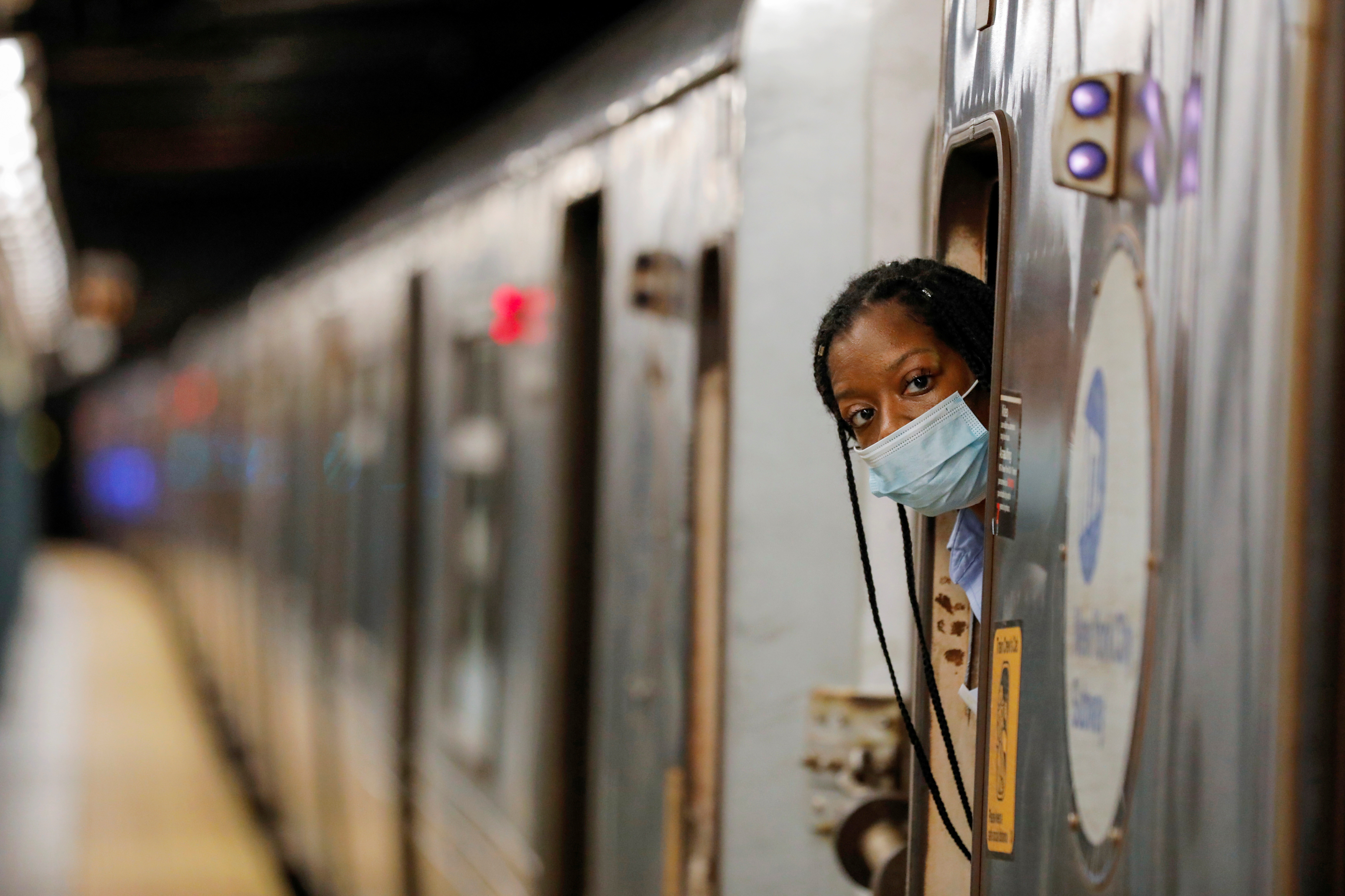An MTA worker is seen wearing a mask on the subway after The Port Authority of New York and New Jersey and the Metropolitan Transportation Authority (MTA) announced a mandatory coronavirus vaccination or weekly test mandate for employees in New York City, New York, U.S., August 2, 2021. REUTERS/Andrew Kelly - RC22XO9OQ7R0