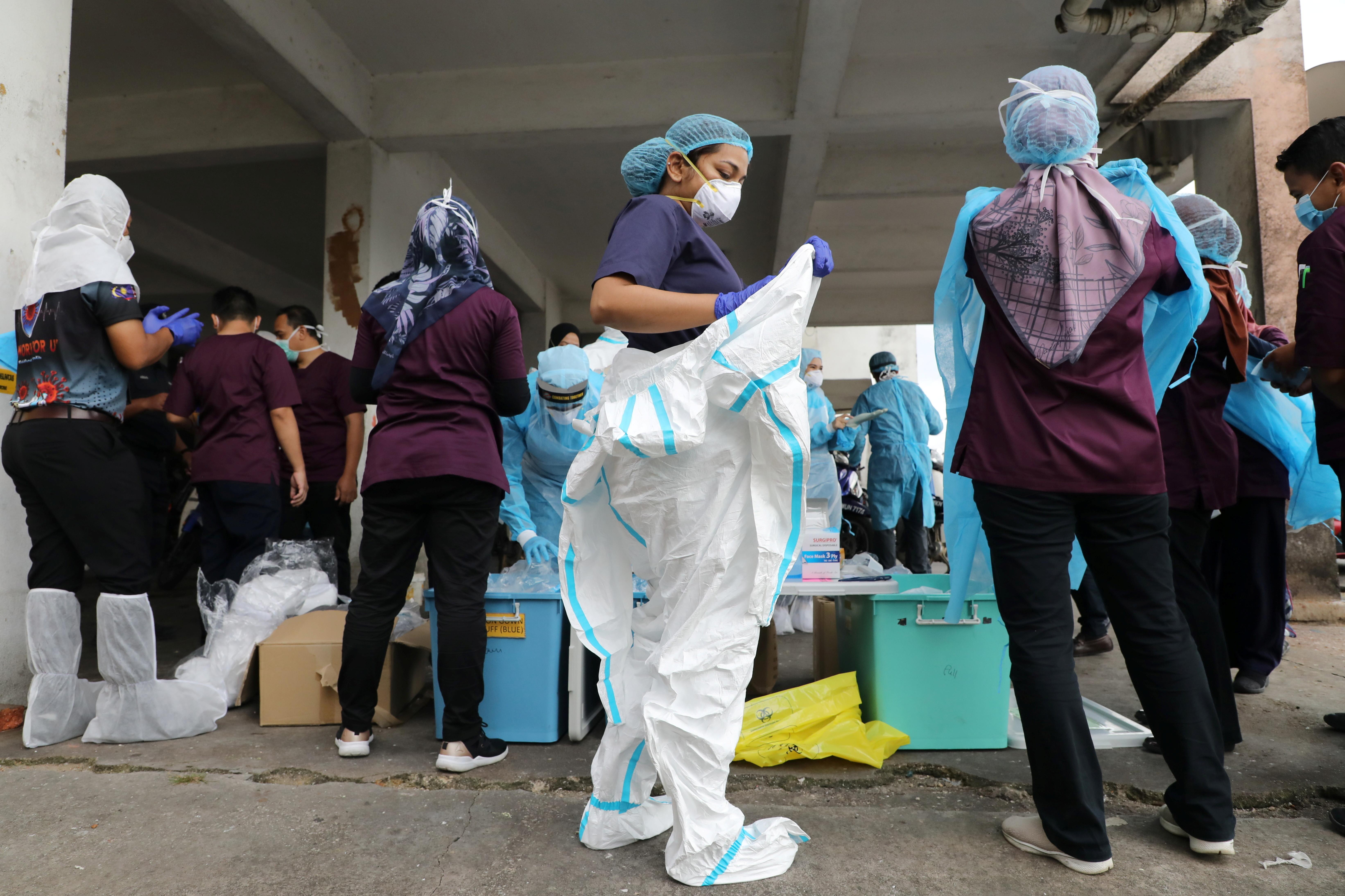 Medical workers put on personal protective equipment before a mass coronavirus disease (COVID-19) swab test in Petaling Jaya, Malaysia October 21, 2020. REUTERS/Lim Huey Teng - RC2YMJ9CKP2T