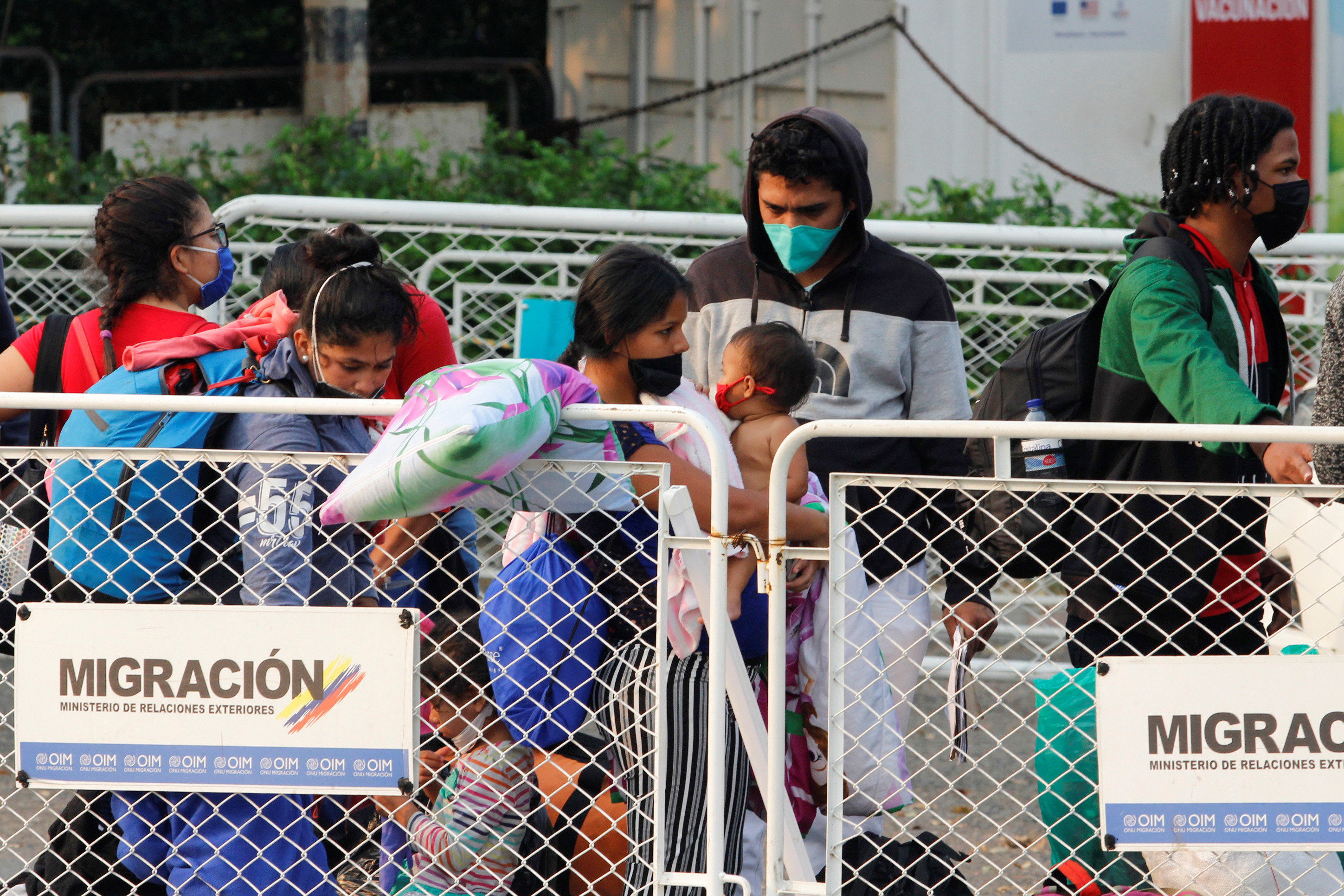 Venezuelan migrants wearing face masks line up at the Simon Bolivar border bridge after travelling on buses assigned by Colombian Migration office for their return to Venezuela, amid the coronavirus disease (COVID-19) outbreak, in Cucuta, Colombia April 15, 2020. REUTERS/Mario Caicedo. NO RESALES. NO ARCHIVES. - RC2C5G9U0BRL