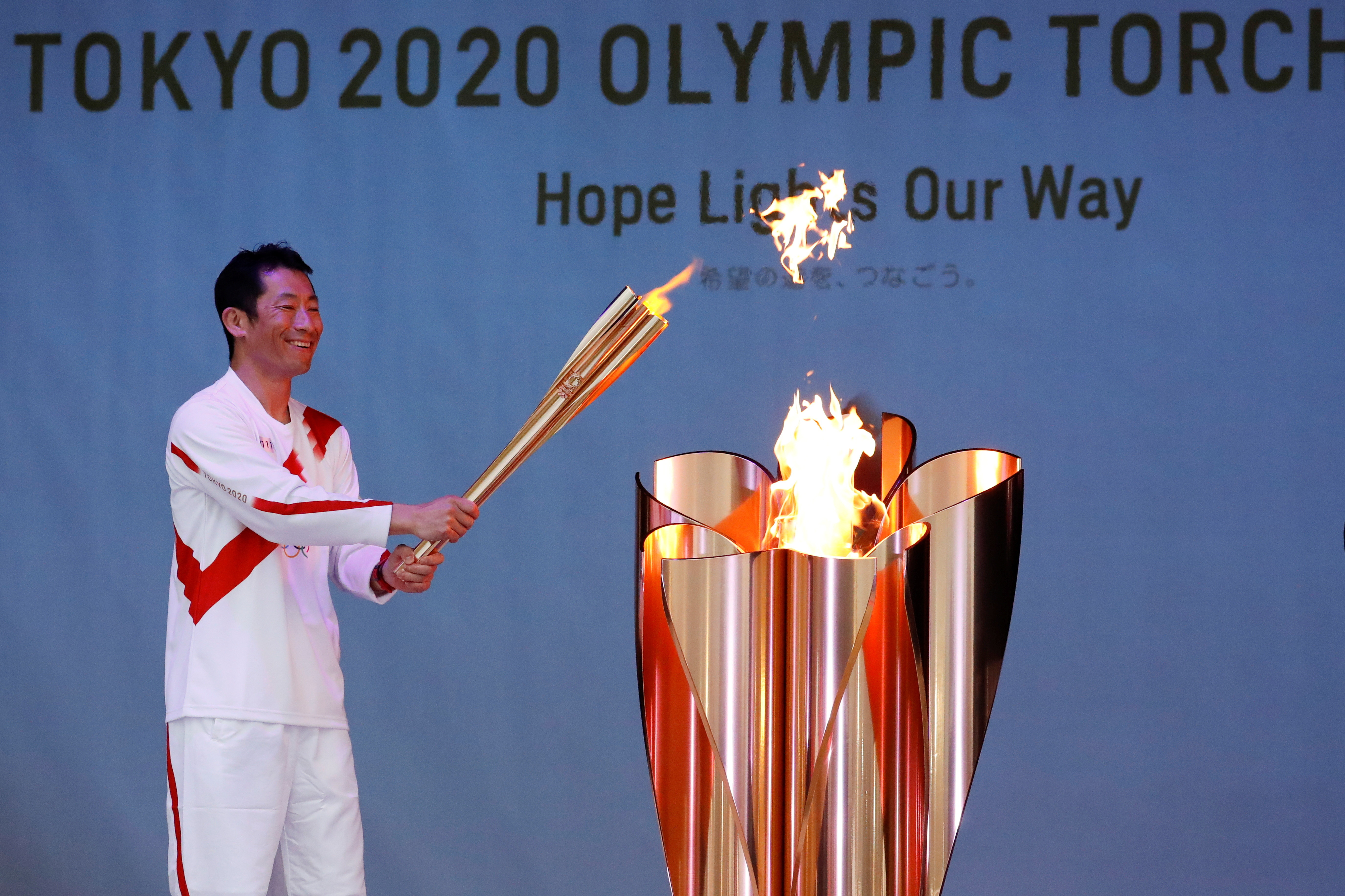 Olympic torch bearer Yoshihide Muroya, Japanese aerobatics pilot and race pilot of the Red Bull Air Race World Championship, lights the celebration cauldron at Hibarigahara Festival Site, during the last leg of the first day of the Tokyo 2020 Olympic torch relay, in Minamisoma, Fukushima prefecture, Japan, March 25, 2021.