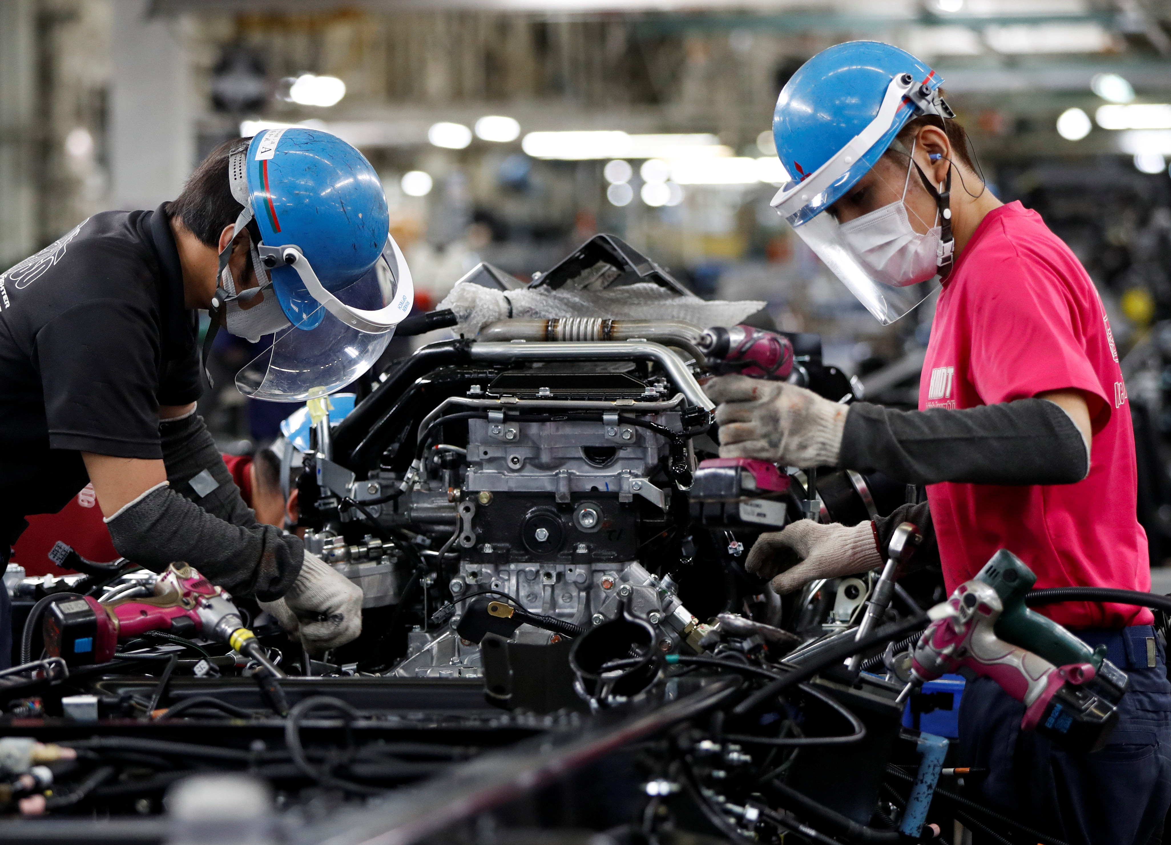 Employees wearing protective face masks and face guards work on the automobile assembly line as the maker ramps up car production with new security and health measures as a step to resume full operations, during the outbreak of the coronavirus disease (COVID-19), at Kawasaki factory of Mitsubishi Fuso Truck and Bus Corp., owned by Germany-based Daimler AG, in Kawasaki, south of Tokyo, Japan May 18, 2020