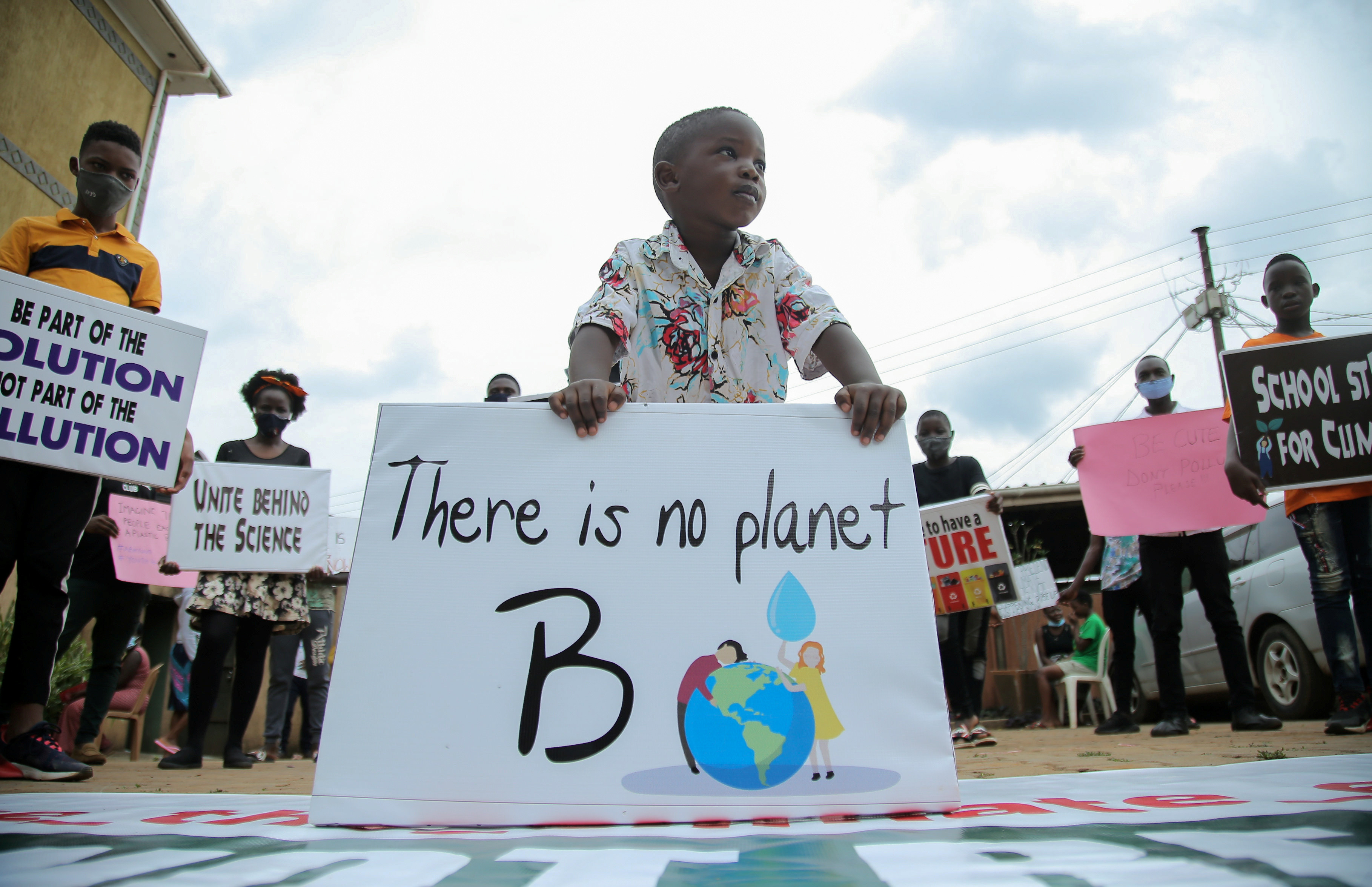 A child stands among Ugandan climate change activists holding placards advocating for climate change as they stand in a formation during a demonstration for the Global Climate Change in Luzira suburb of Kampala, Uganda, September 25, 2020. REUTERS/Abubaker Lubowa - RC2Q5J9EWCKT
