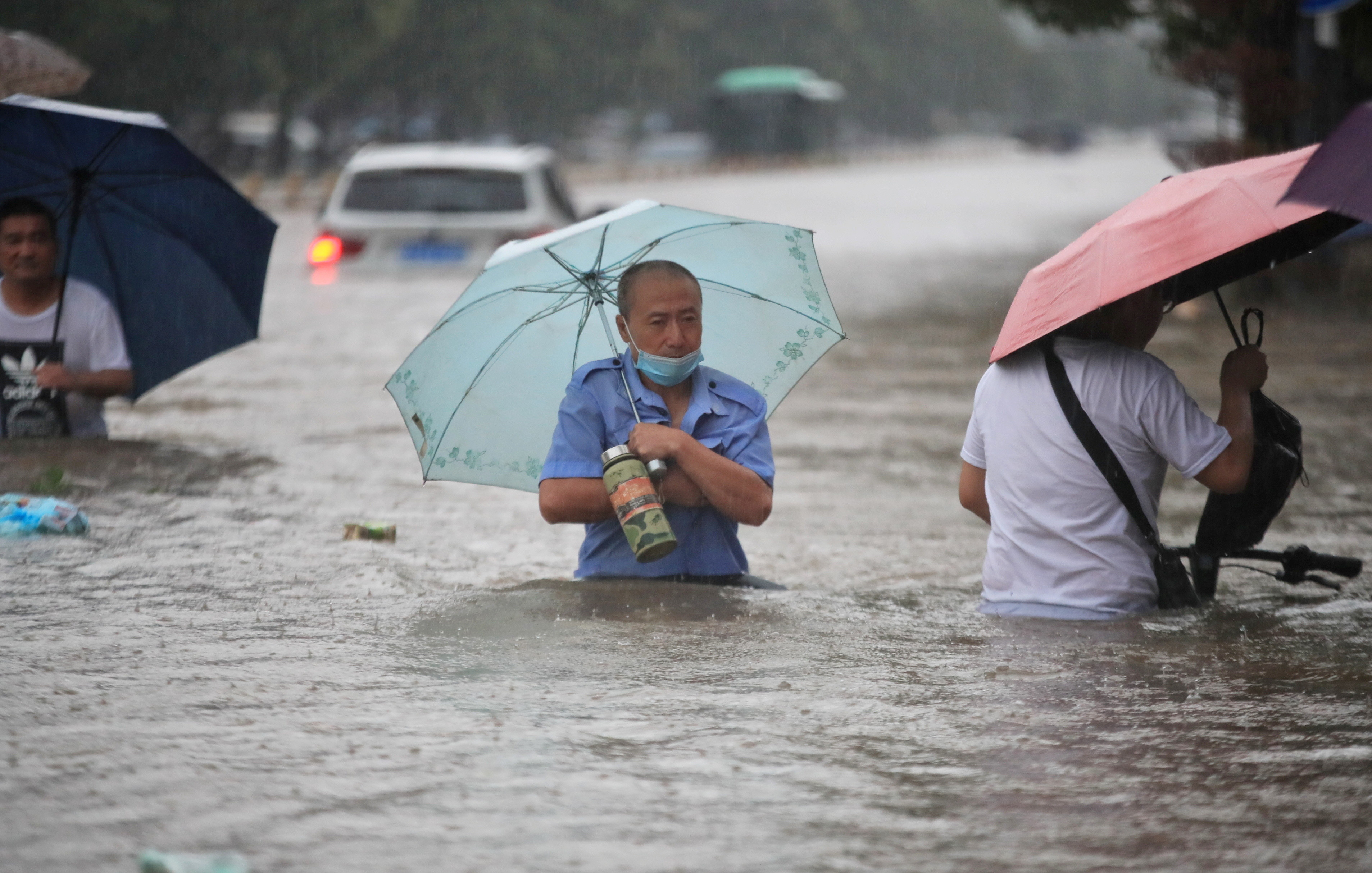 Residents wade through floodwaters on a flooded road amid heavy rainfall in Zhengzhou, Henan province
