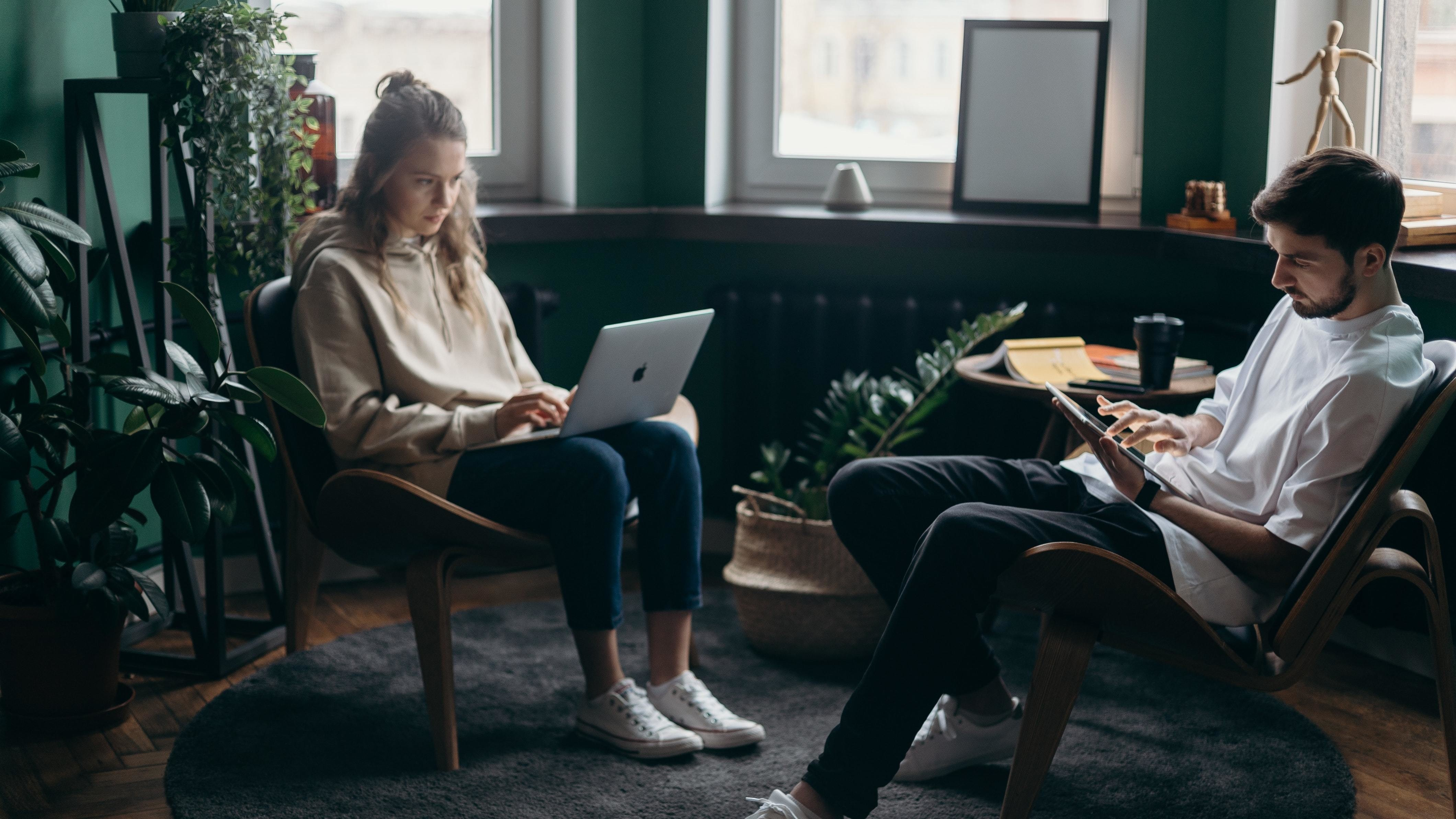 Two young people working from home on digital devices.