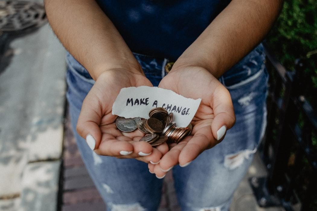 Open hands holding money and a note saying 'make a change.'