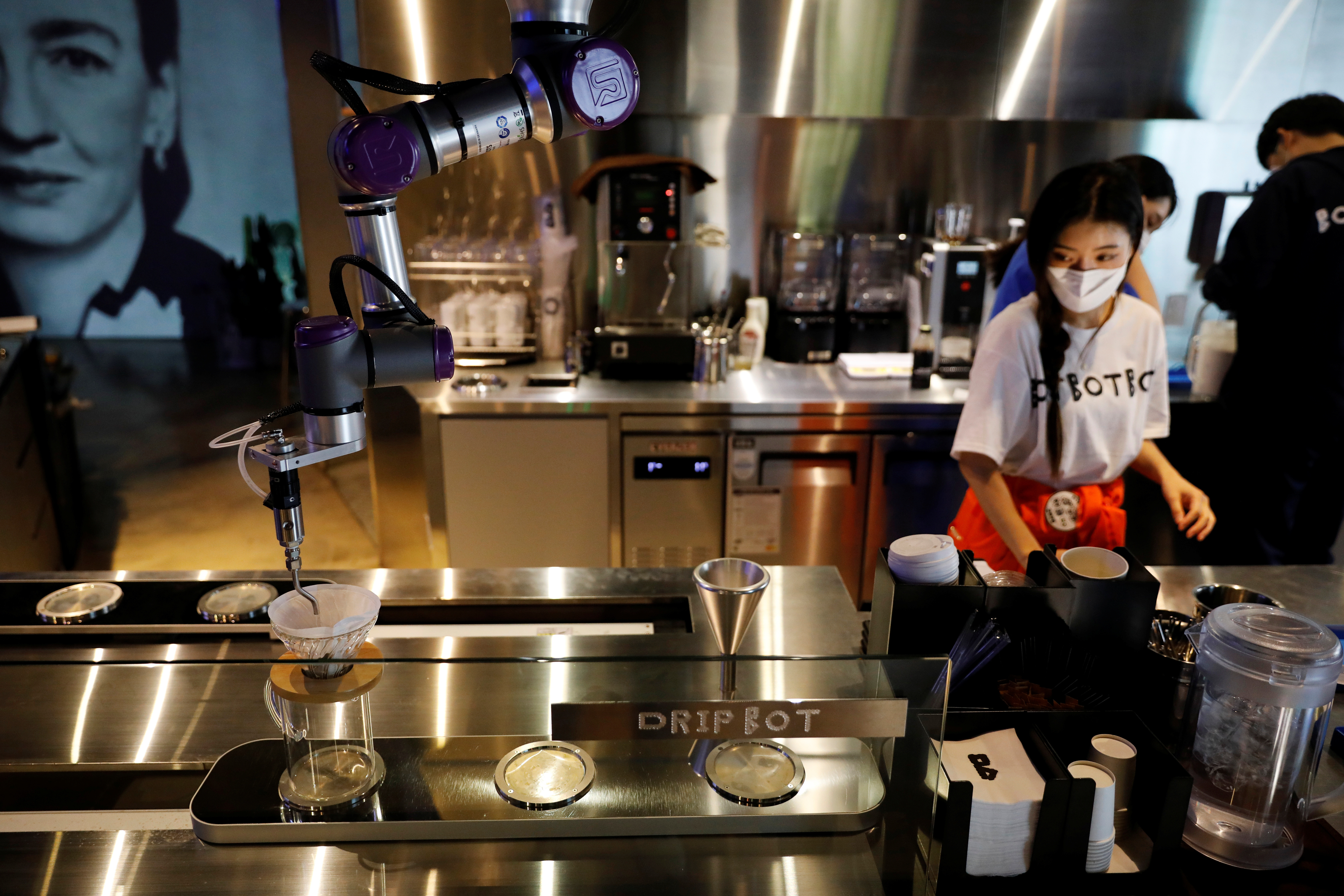 Drip Bot makes a cup of coffee as an employee wearing a mask to avoid the spread of the coronavirus disease (COVID-19) works at a cafe in Seoul, South Korea, June 3, 2020. Picture taken on June 3, 2020.    REUTERS/Kim Hong-Ji - RC222H9JS34E