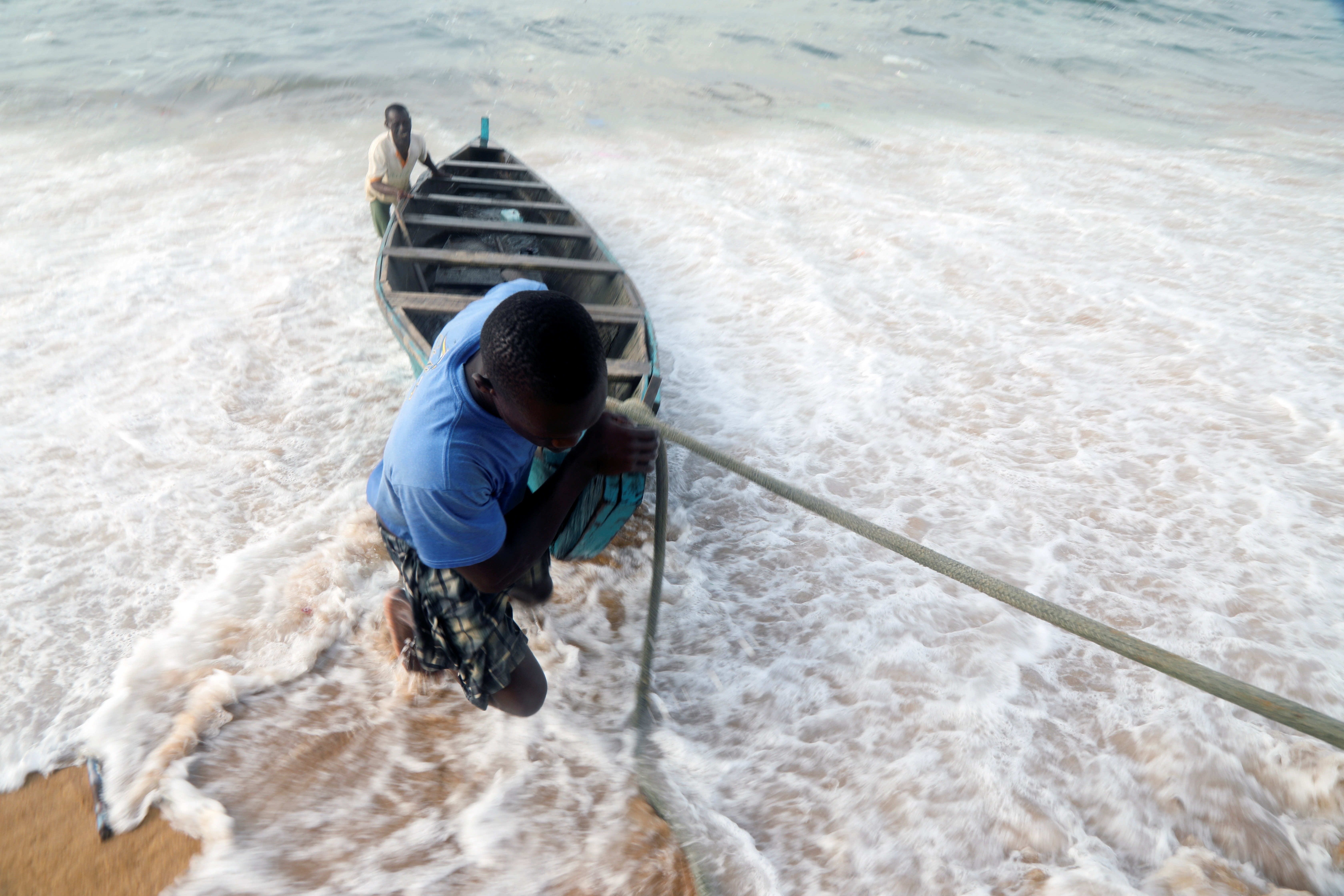 Men pull a boat from the sea at the seashore in a fishing village of Port Bouet in Abidjan, Ivory Coast February 12, 2021.