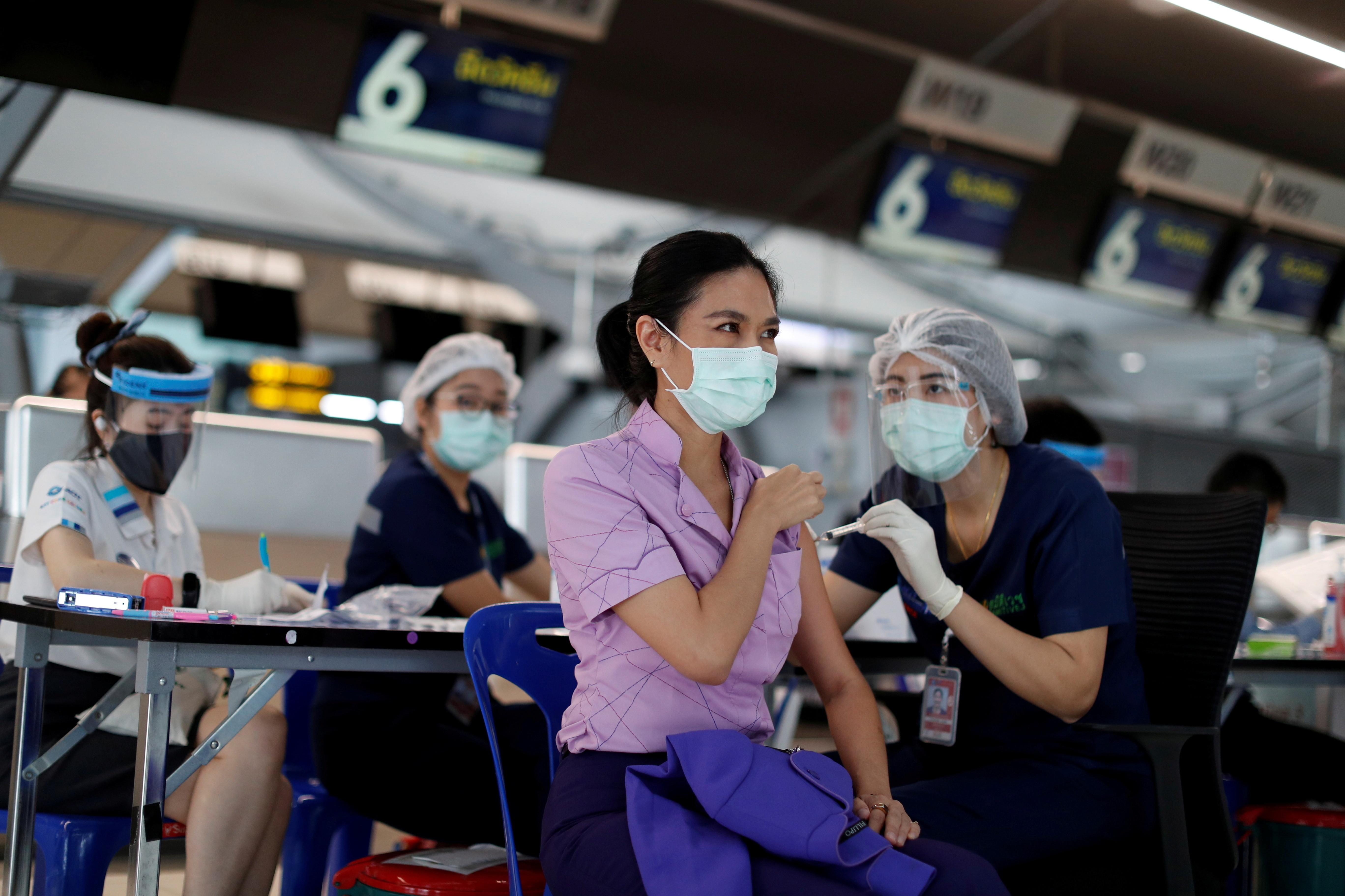 Siradhakan Chotisen, a Thai Airways crew member, receives her vaccination against the coronavirus disease (COVID-19) at Suvarnabhumi airport in Bangkok, Thailand April 28, 2021. REUTERS/Jorge Silva - RC2R4N9GSO3V
