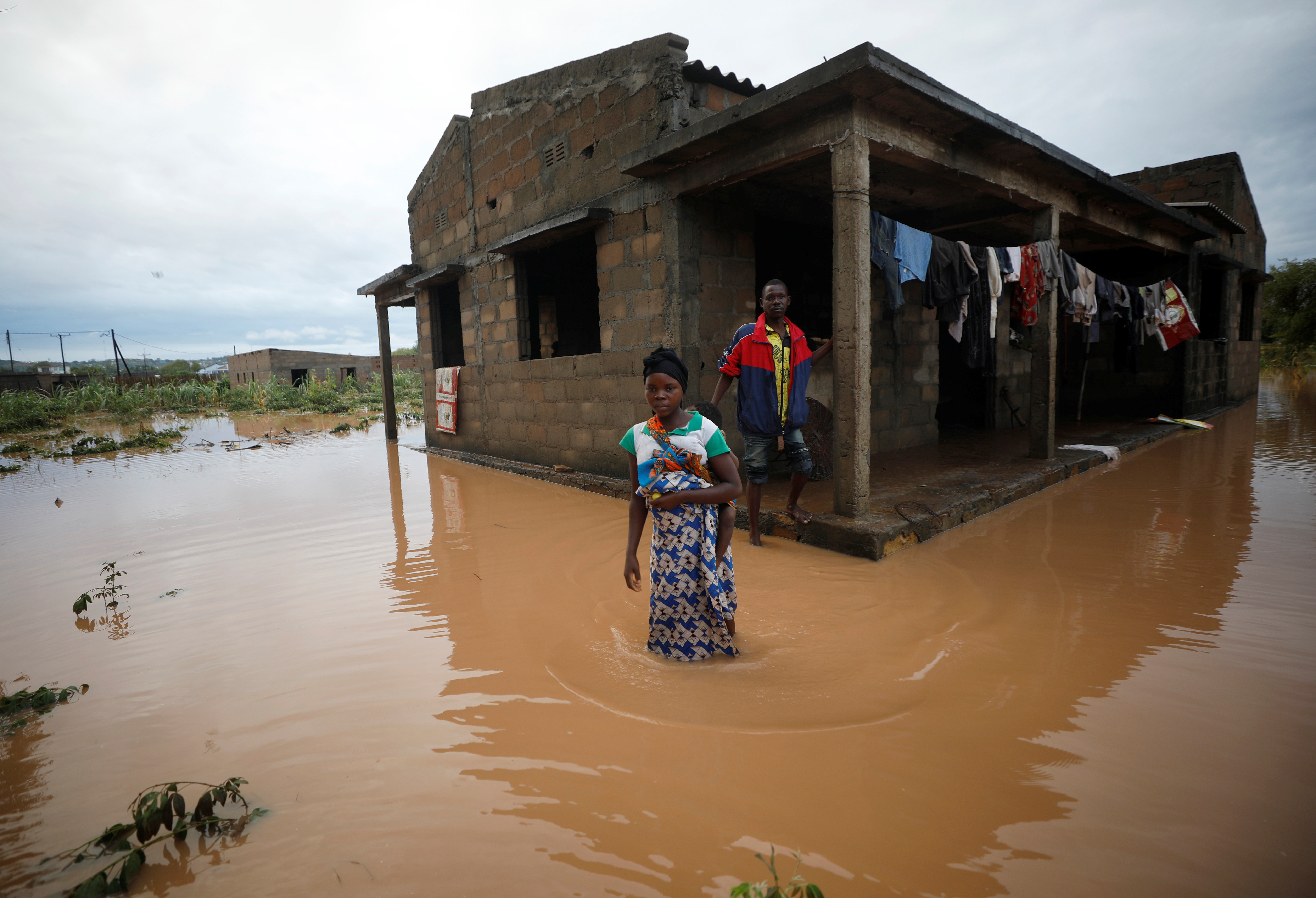 Villagers wade through floodwaters outside their home, flooded in the aftermath of Cyclone Kenneth, at Wimbe village in Pemba, Mozambique.