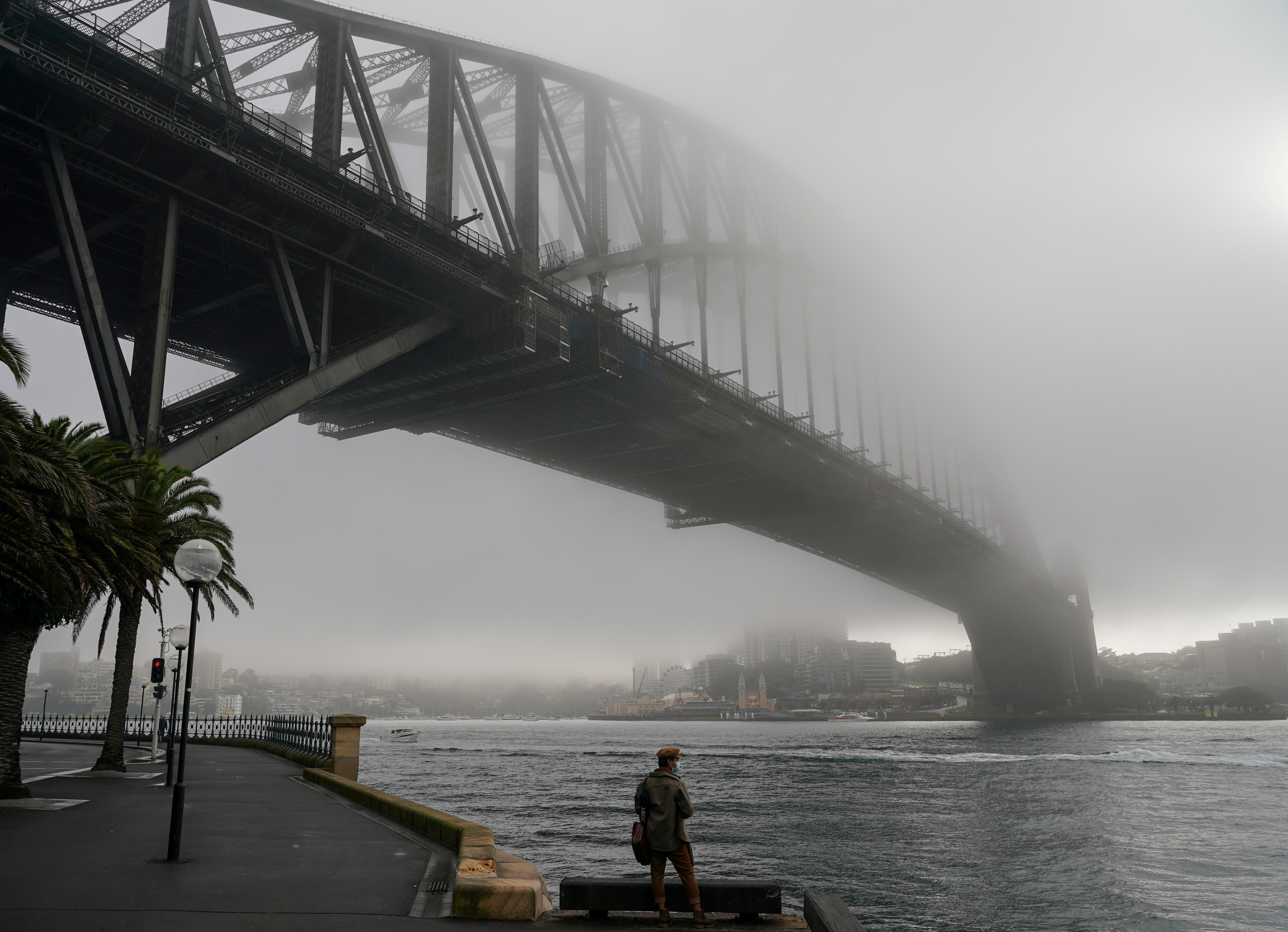 A man wearing a protective face mask takes in the waterfront view underneath the Sydney Harbour Bridge, seen shrouded in fog, during a lockdown to curb the spread of a coronavirus disease (COVID-19) outbreak in Sydney, Australia, June 30, 2021. REUTERS/Loren Elliott     TPX IMAGES OF THE DAY - RC2NAO9MCMR5