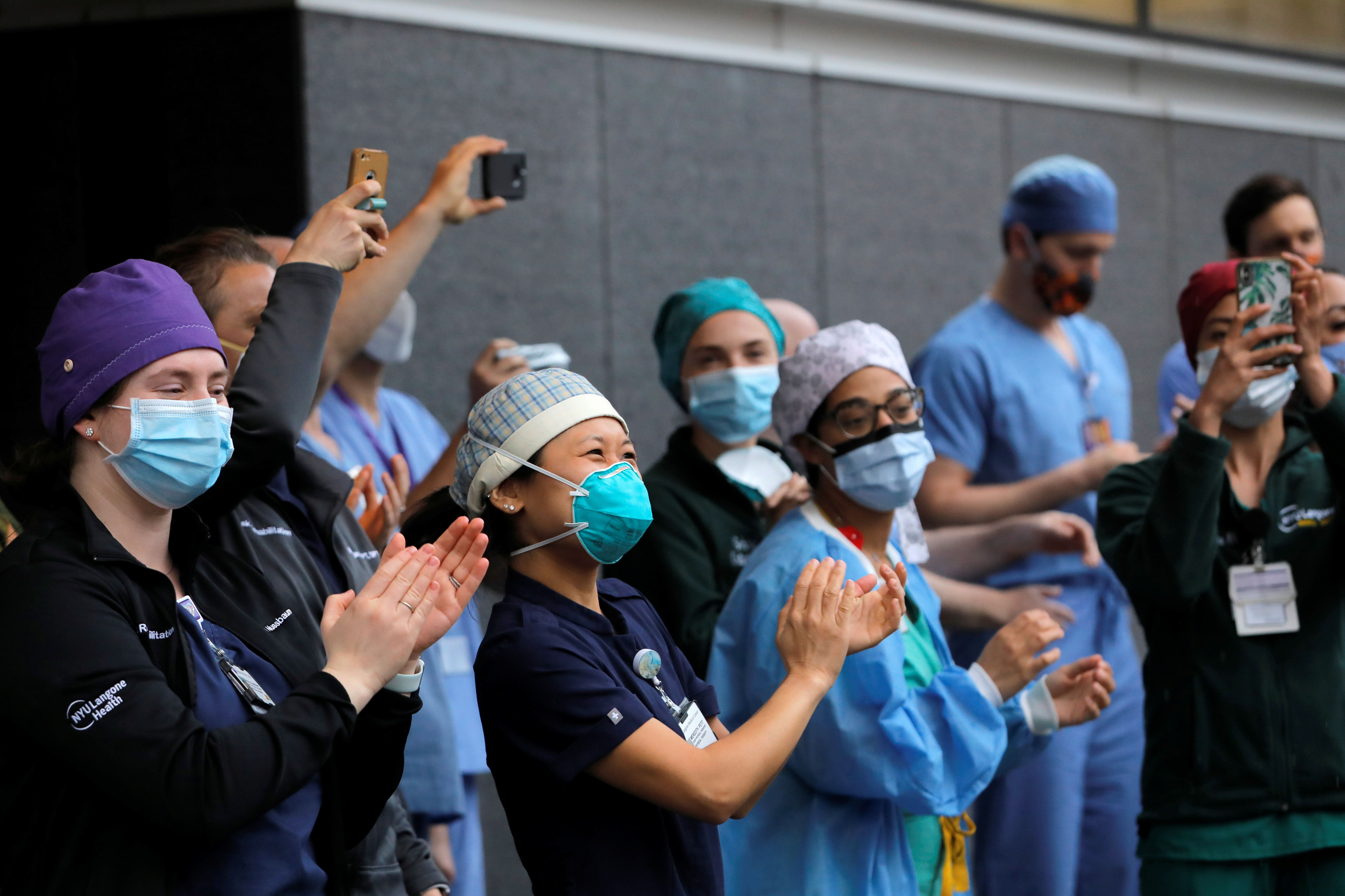 Healthcare workers react as people clap for them on National Nurse Day outside NYU Langone Health during the outbreak of the coronavirus disease (COVID-19) in the Manhattan borough of New York City, U.S., May 6, 2020. REUTERS/Andrew Kelly - RC2BJG9A82KZ
