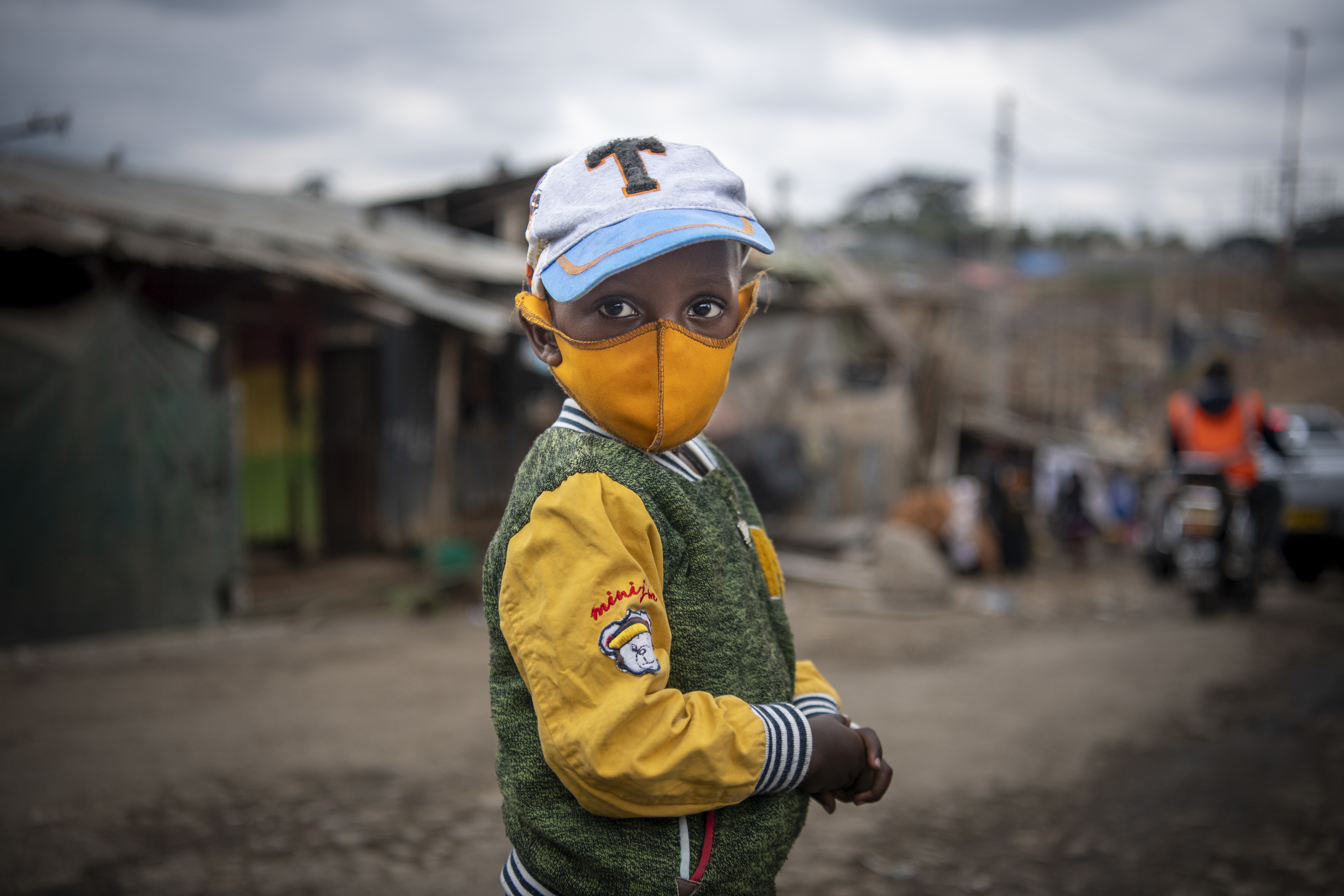 """A rare young boy wears a face mask as he walks with his mother on the streets of Mathare informal settlement. School has been declared """"null and void"""" for the year of 2020 and kids are left to fend for themselves on the streets, often needing to beg, work and steal for food.  Nairobi, Kenya."""