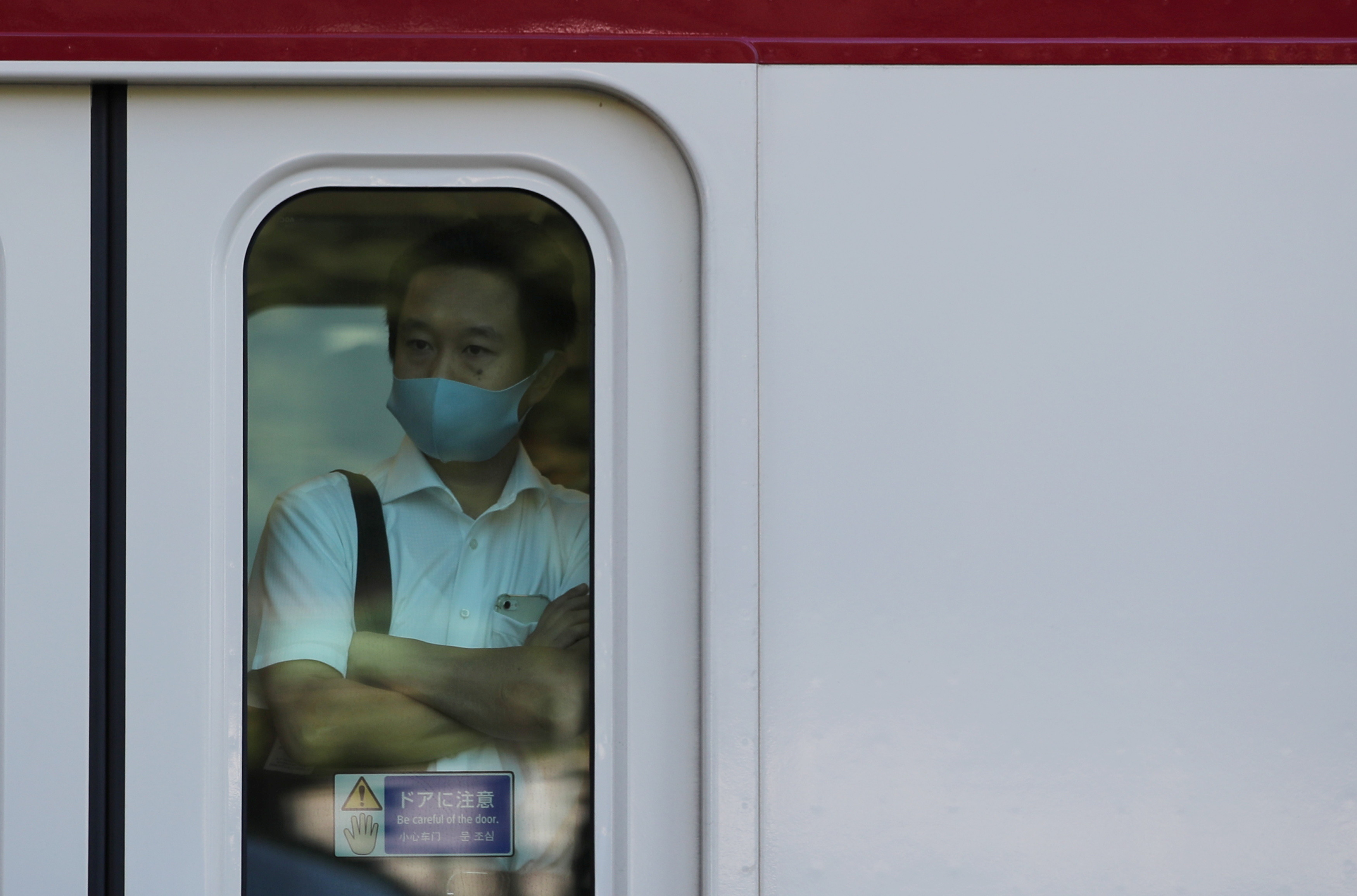 A man wearing a protective mask rides a train, amid the coronavirus disease (COVID-19) outbreak, in Tokyo, Japan, August 10, 2021.   REUTERS/Kim Kyung-Hoon - RC2Z1P9IZ464