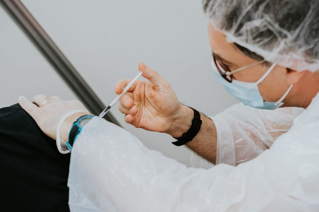 Doctor injects vaccine with surgical needle.