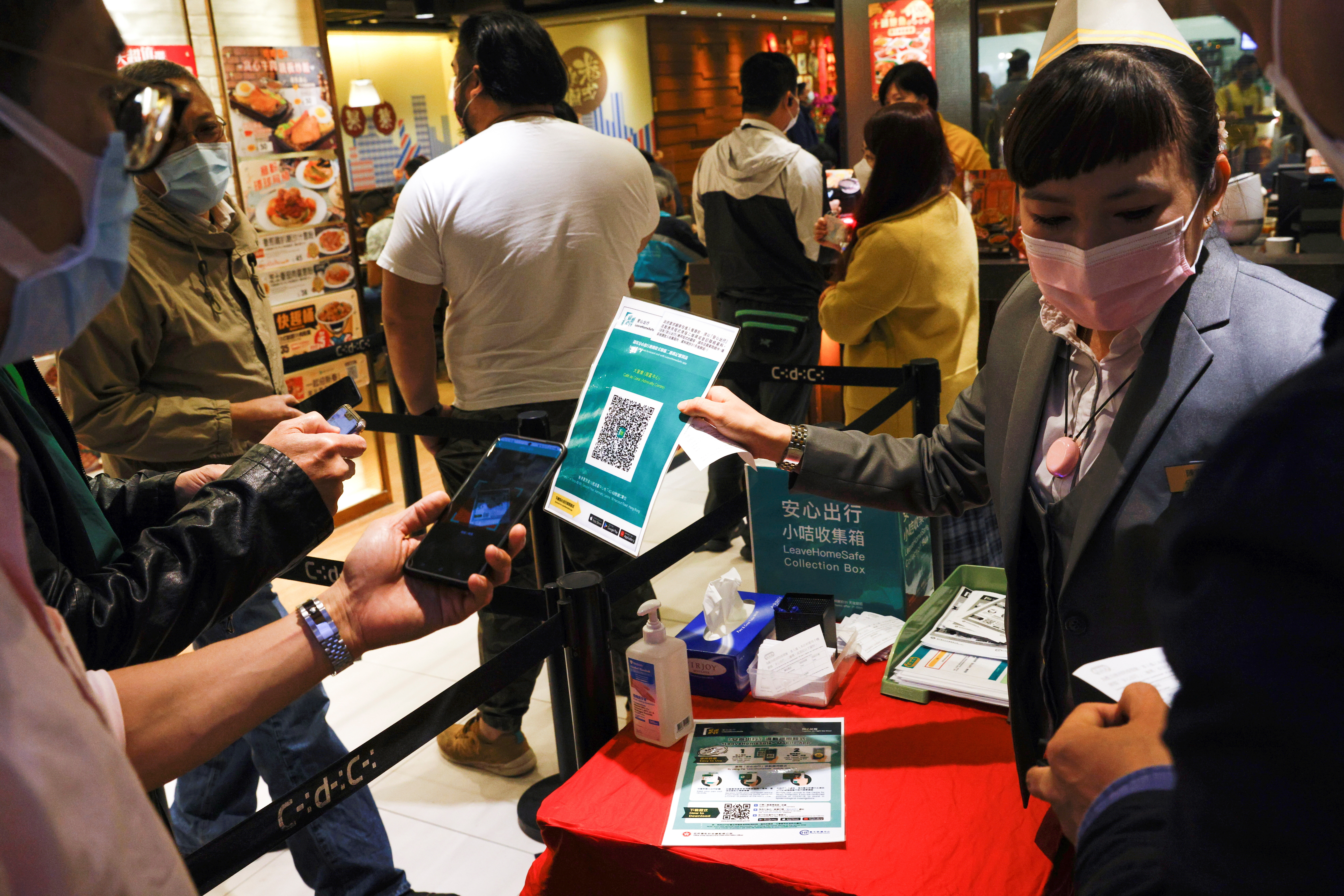 """A staff member holds a QR code for the """"LeaveHomeSafe"""" COVID-19 contact-tracing app to consumers at a restaurant, following the coronavirus disease (COVID-19) outbreak, in Hong Kong, China February 18, 2021. REUTERS/Tyrone Siu - RC2TUL9H0U2N"""