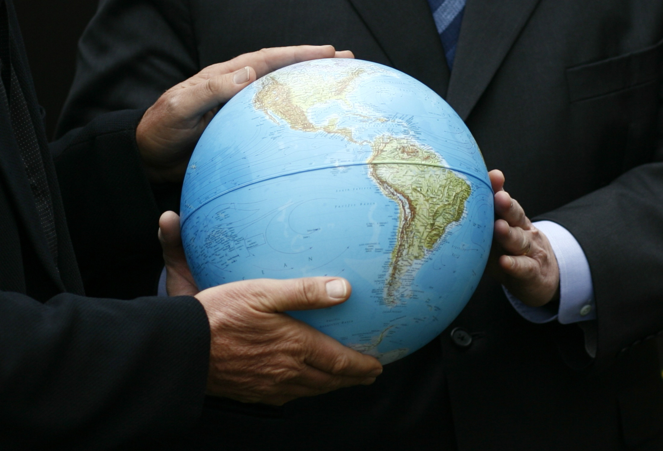 a close up shot of a globe being held by men in suits