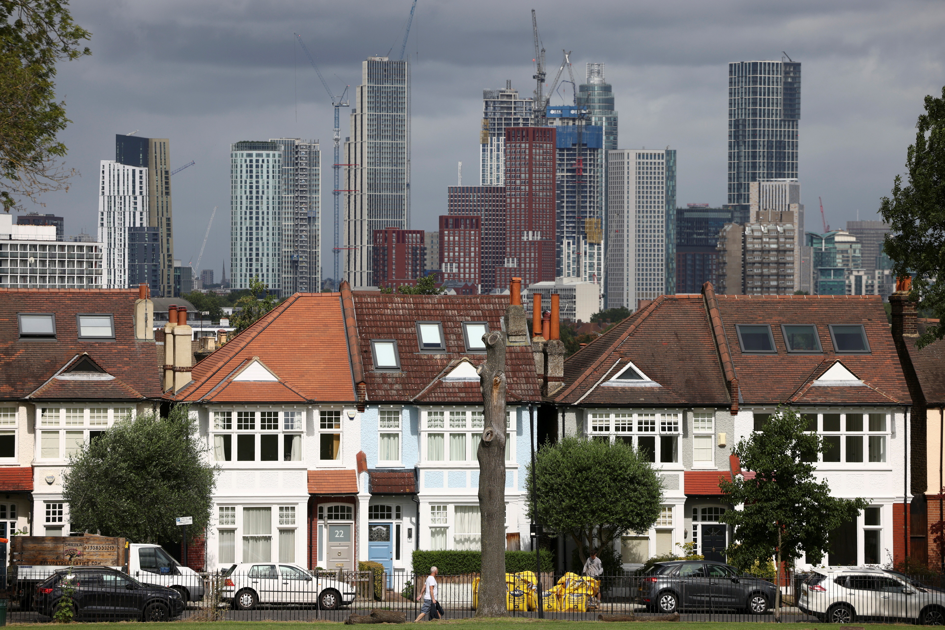High-rise apartments under construction can be seen in the distance behind a row of residential housing in south London, Britain, August 6, 2021. REUTERS/Henry Nicholls - RC2MZO96C6E3