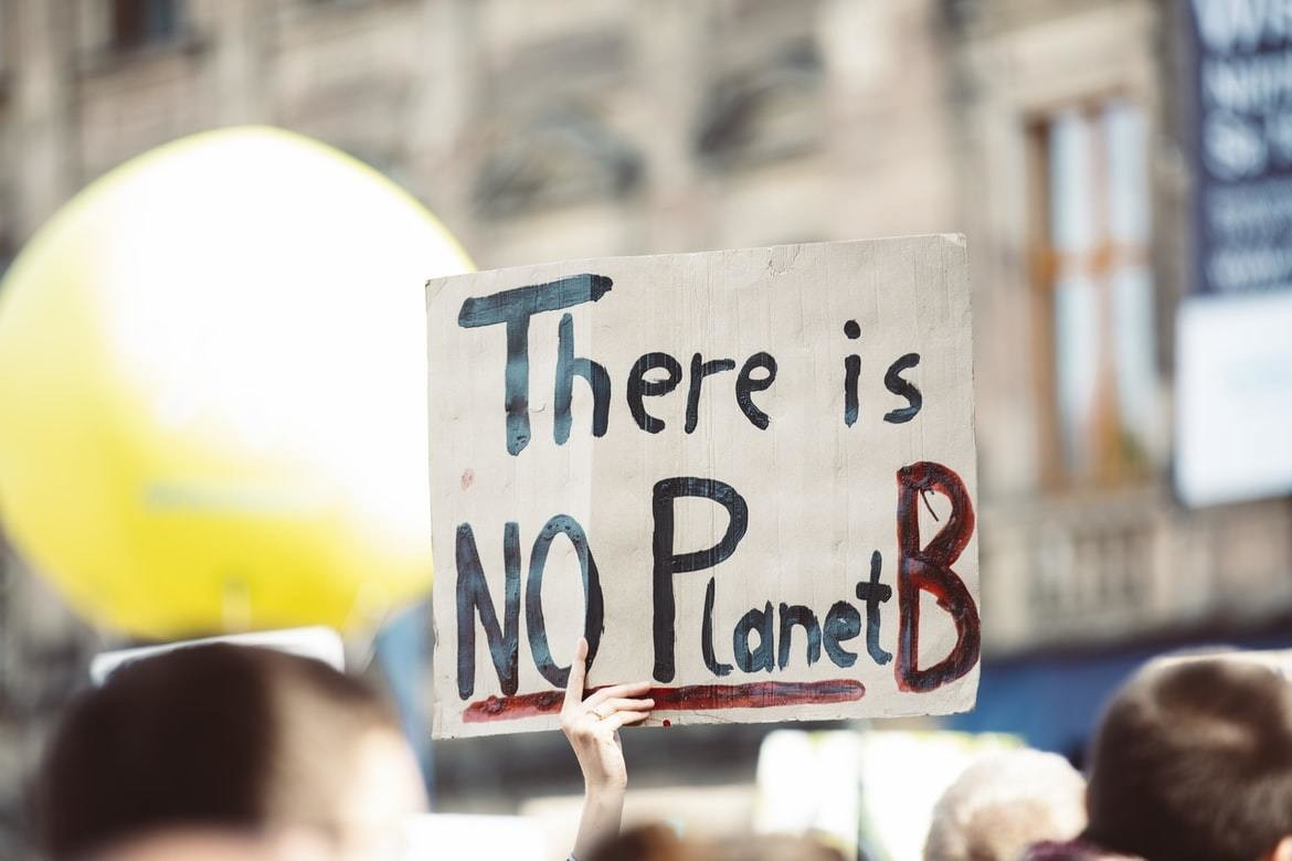 A hand holding a sign saying 'There is no Planet B'