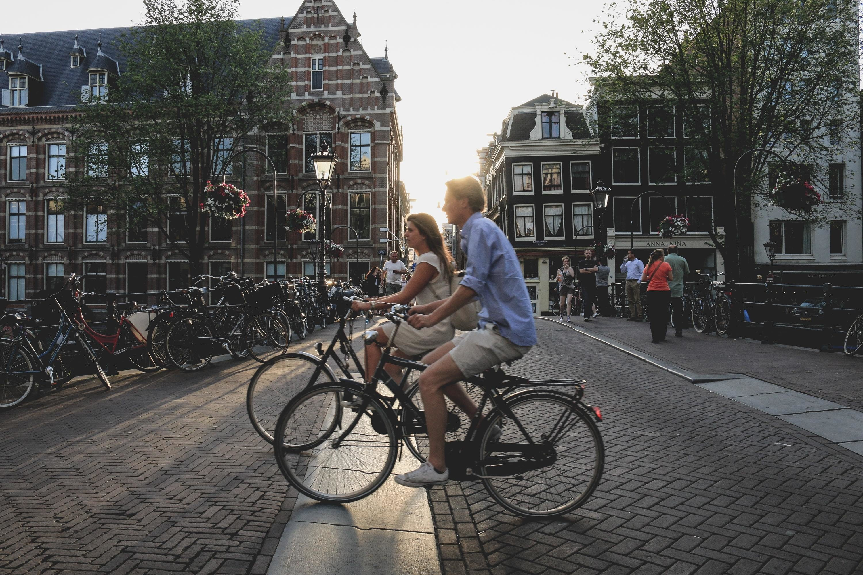 image of two people riding bikes in Amsterdam, with lots of bikes parked up behind them