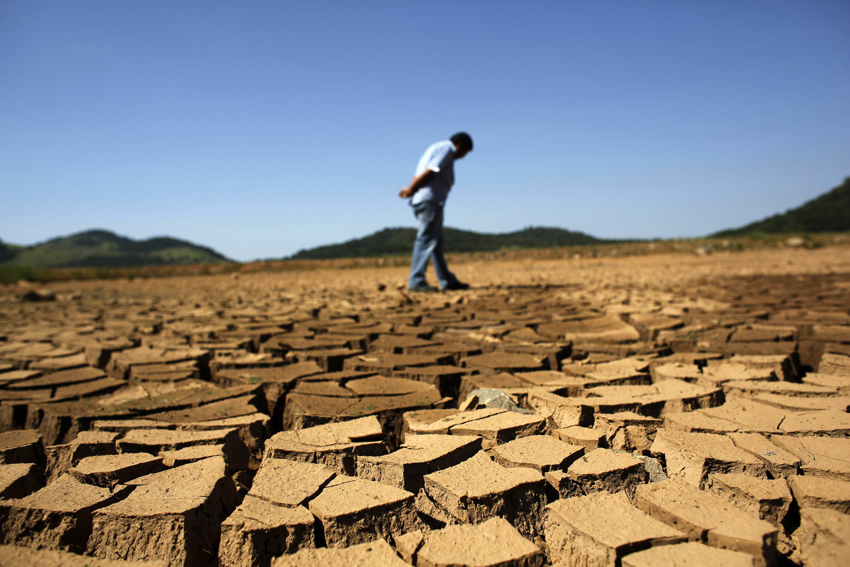 a worker of the Brazilian enterprise of Sao Paulo state, that provides water and sewage services to residential, commercial and industrial areas looks at the cracked ground of Jaguary dam in Braganca Paulista, 100 km from Sao Paulo January 31, 2014. This has been the hottest January on record in parts of Brazil, and the heat plus a severe drought has fanned fears of water shortages, crop damage, and higher electricity bills