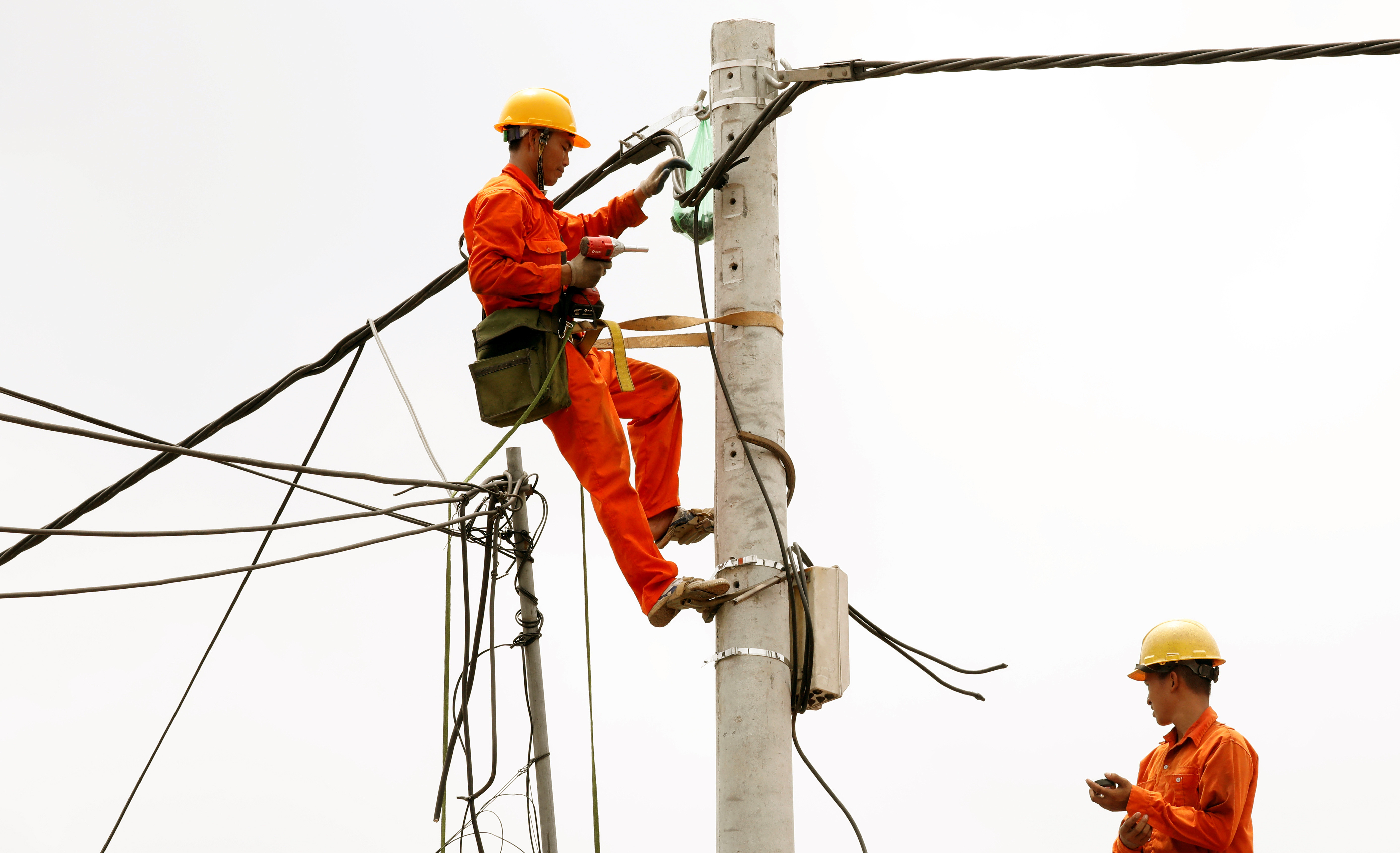 image of a worker repairing an electric grid