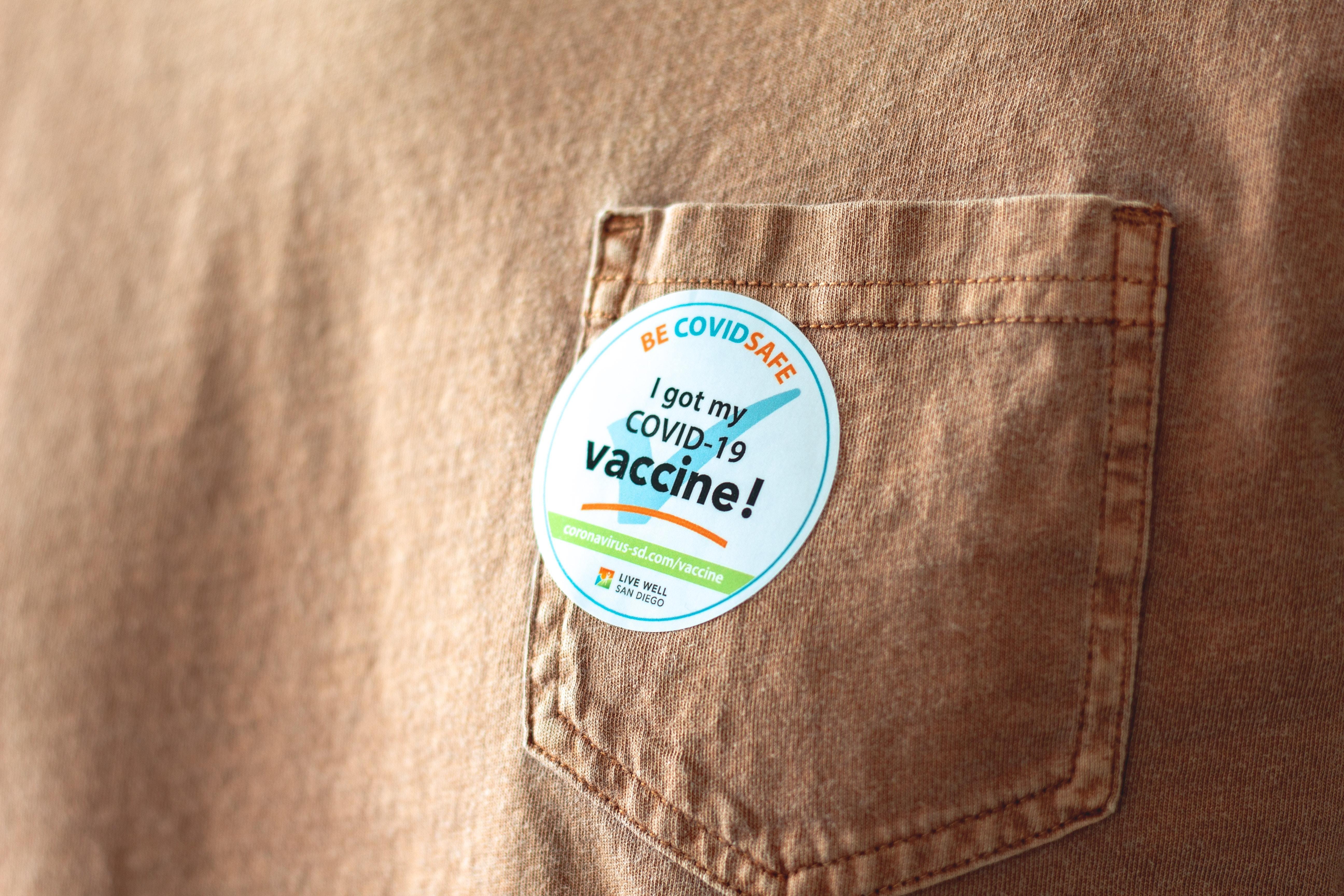 """I got my COVID-19 vaccine"" sticker, light brown shirt; mass vaccination."
