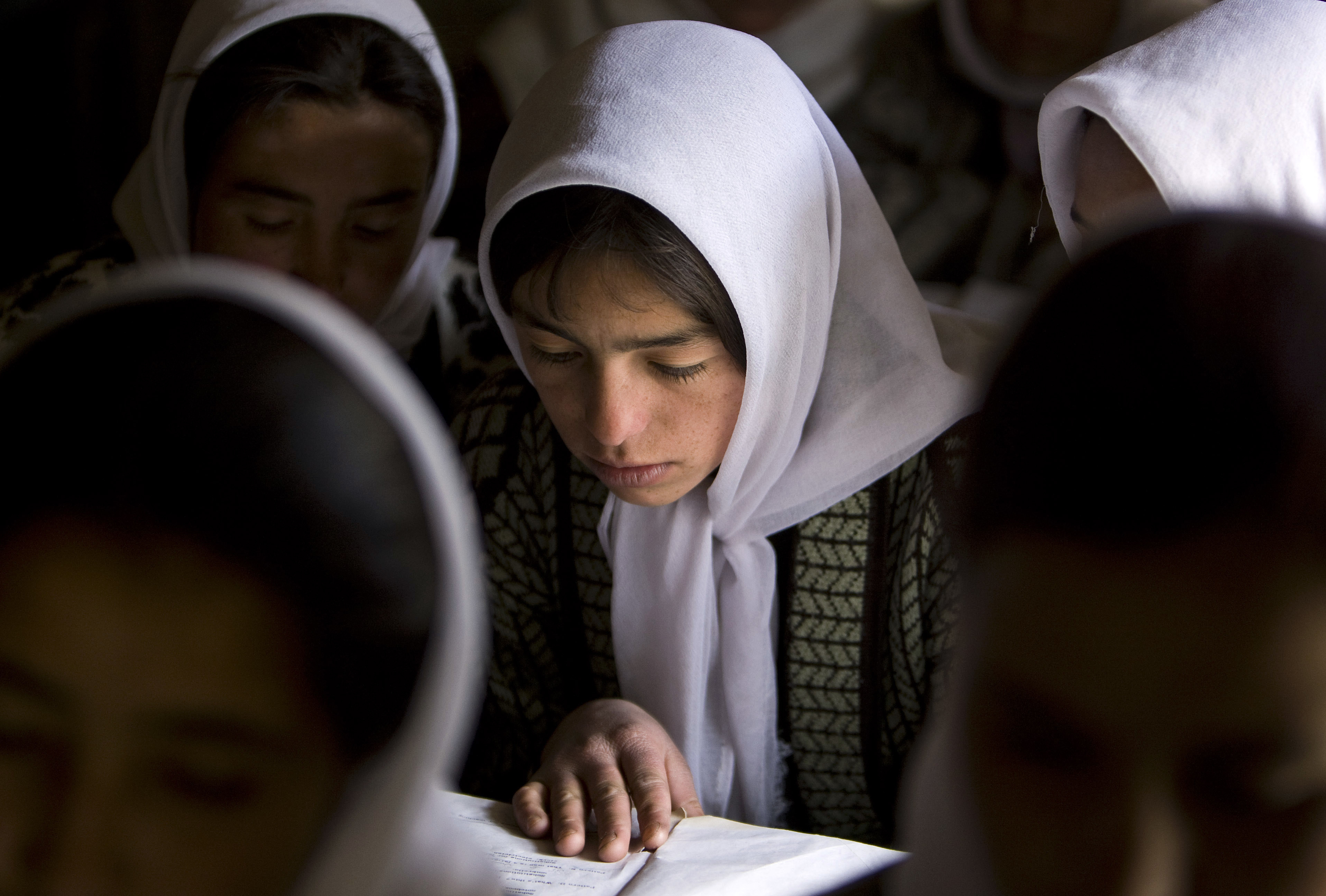 An Afghan girl reads a book in a classroom among other female students